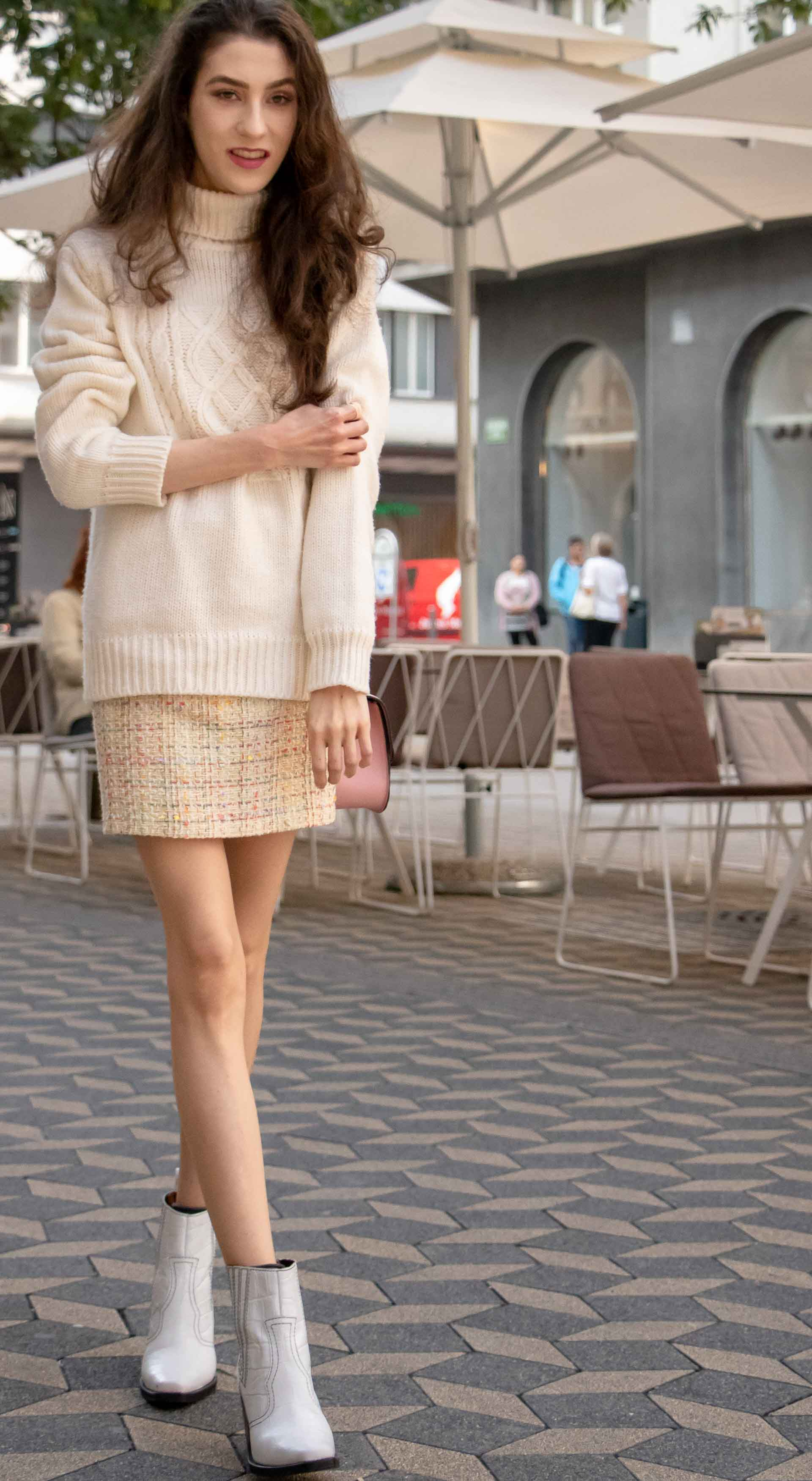 Beautiful Slovenian Fashion Blogger Veronika Lipar of Brunette from Wall dressed in white Ganni Western boots, yellow tweed skirt, white turtleneck sweater, chain strap shoulder bag for autumnal brunch
