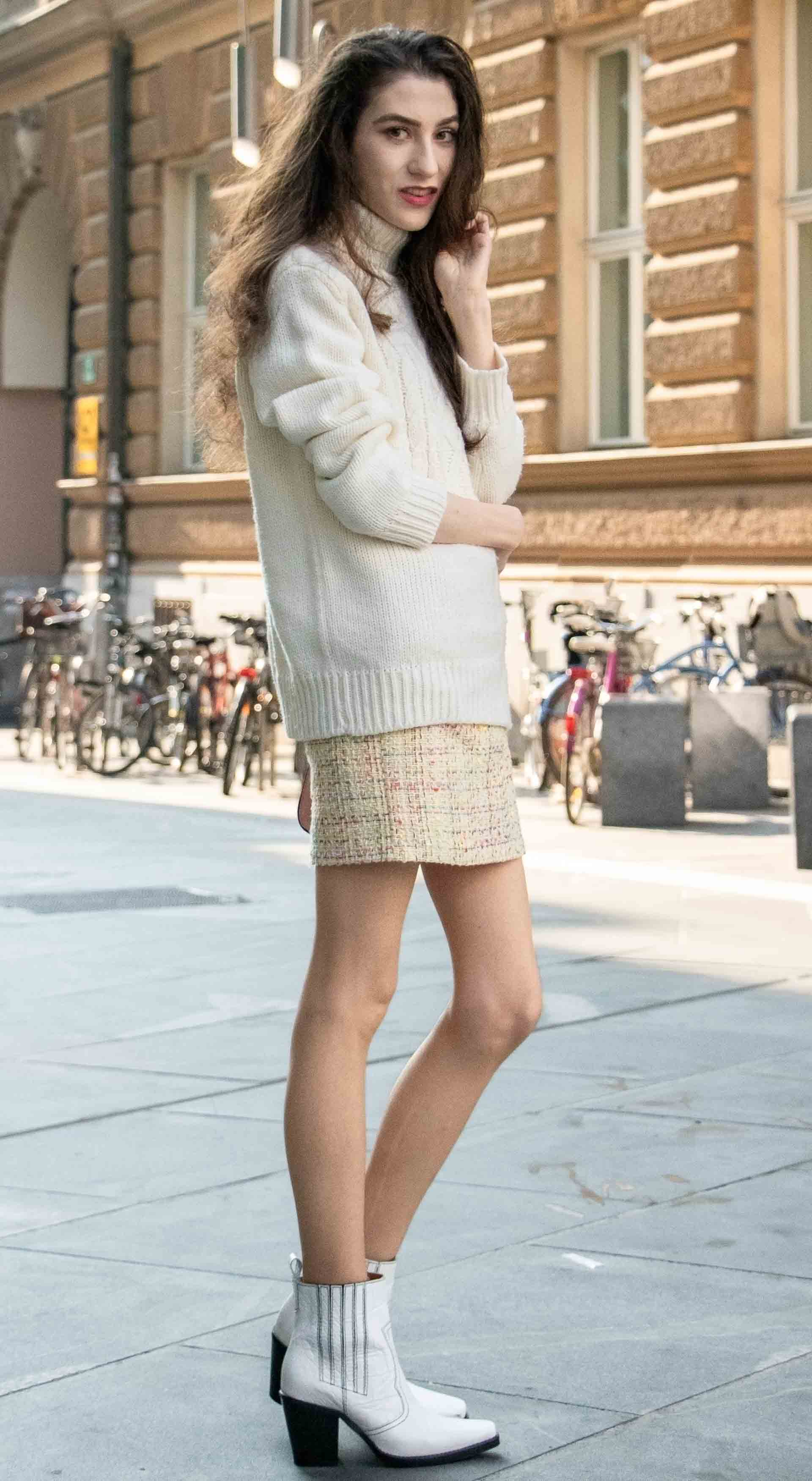 Beautiful Slovenian Fashion Blogger Veronika Lipar of Brunette from Wall wearing white Ganni Western boots, yellow tweed skirt, white turtleneck sweater, chain strap shoulder bag on the street in the morning in Ljubljana in fall
