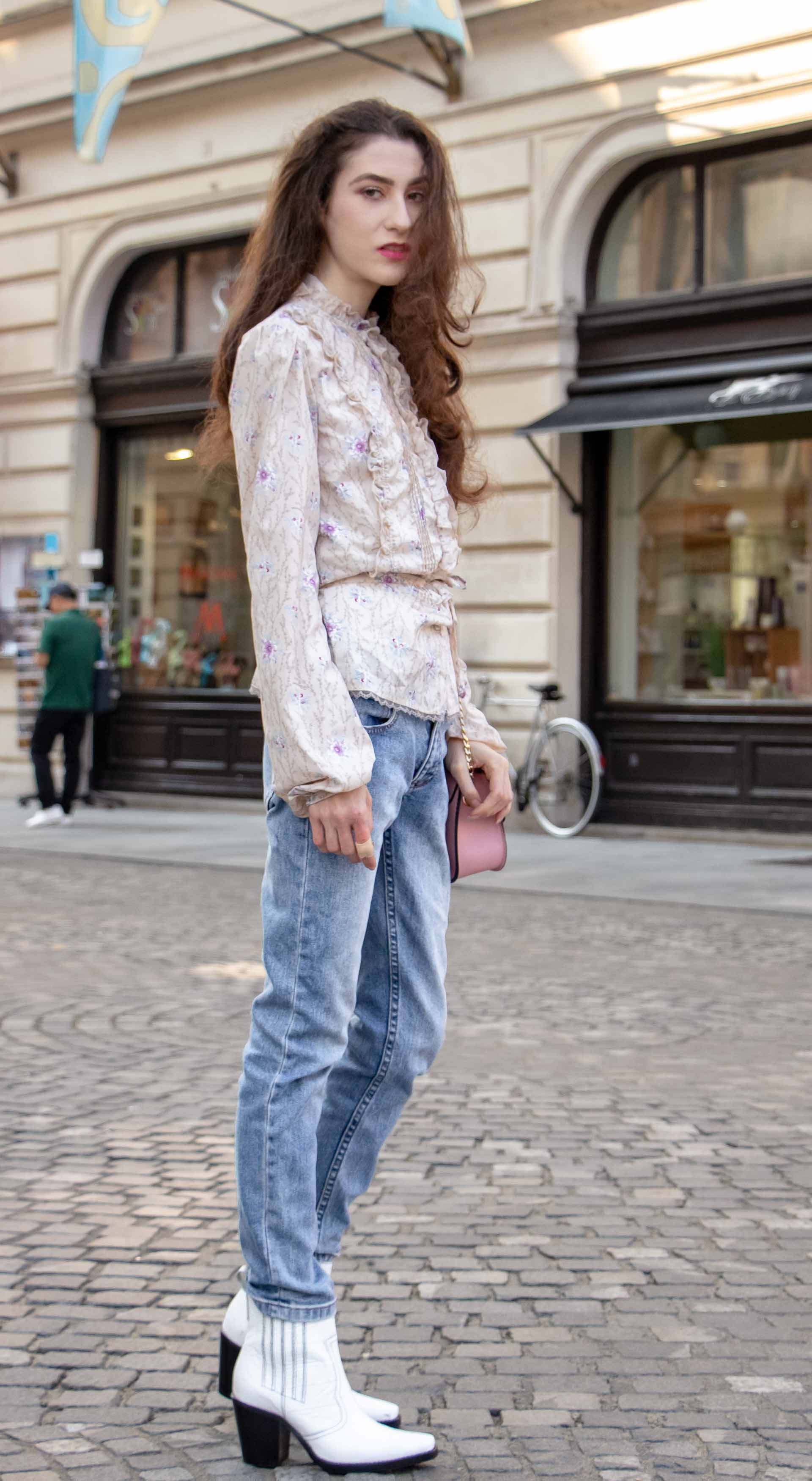 Beautiful Slovenian Fashion Blogger Veronika Lipar of Brunette from Wall dressed in white Ganni Western boots, floral long sleeved Prairie shirt, A.P.C. blue jeans on the street in autumn in Ljubljana
