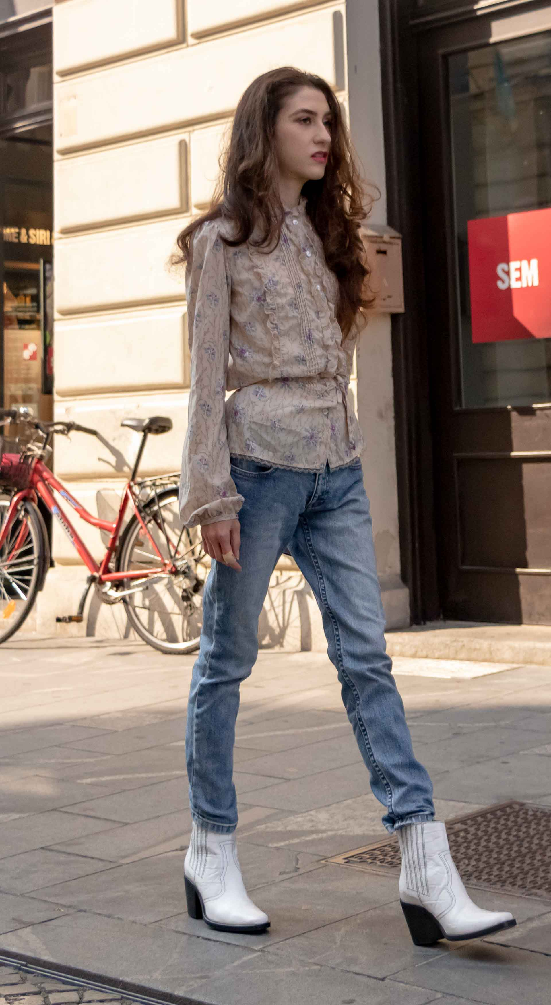 Beautiful Slovenian Fashion Blogger Veronika Lipar of Brunette from Wall dressed in white Ganni Western boots, floral long sleeved Prairie shirt, A.P.C. blue jeans walking on the street in fall in Ljubljana