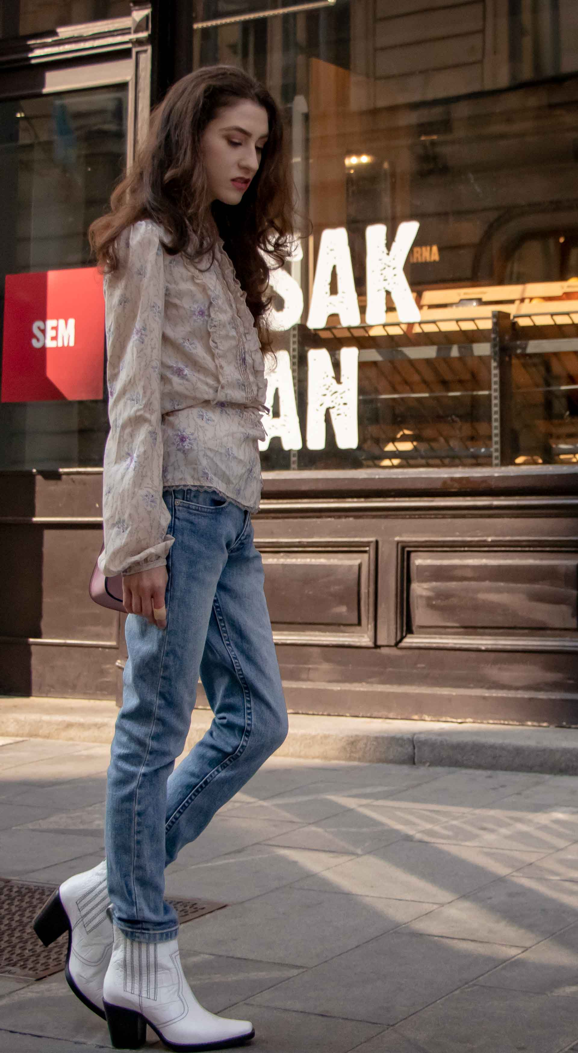 Beautiful Slovenian Fashion Blogger Veronika Lipar of Brunette from Wall dressed in white Ganni Western boots, floral long sleeved Prairie shirt, A.P.C. blue jeans on the street in fall in Ljubljana