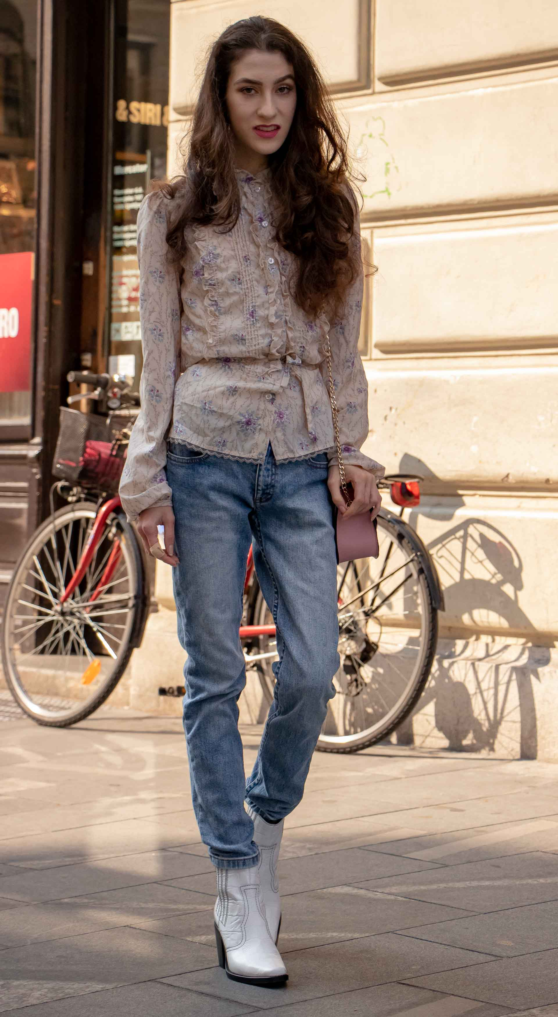 Beautiful Slovenian Fashion Blogger Veronika Lipar of Brunette from Wall wearing white Ganni Western boots, floral long sleeved Prairie shirt, A.P.C. blue jeans on the street in autumn in Ljubljana