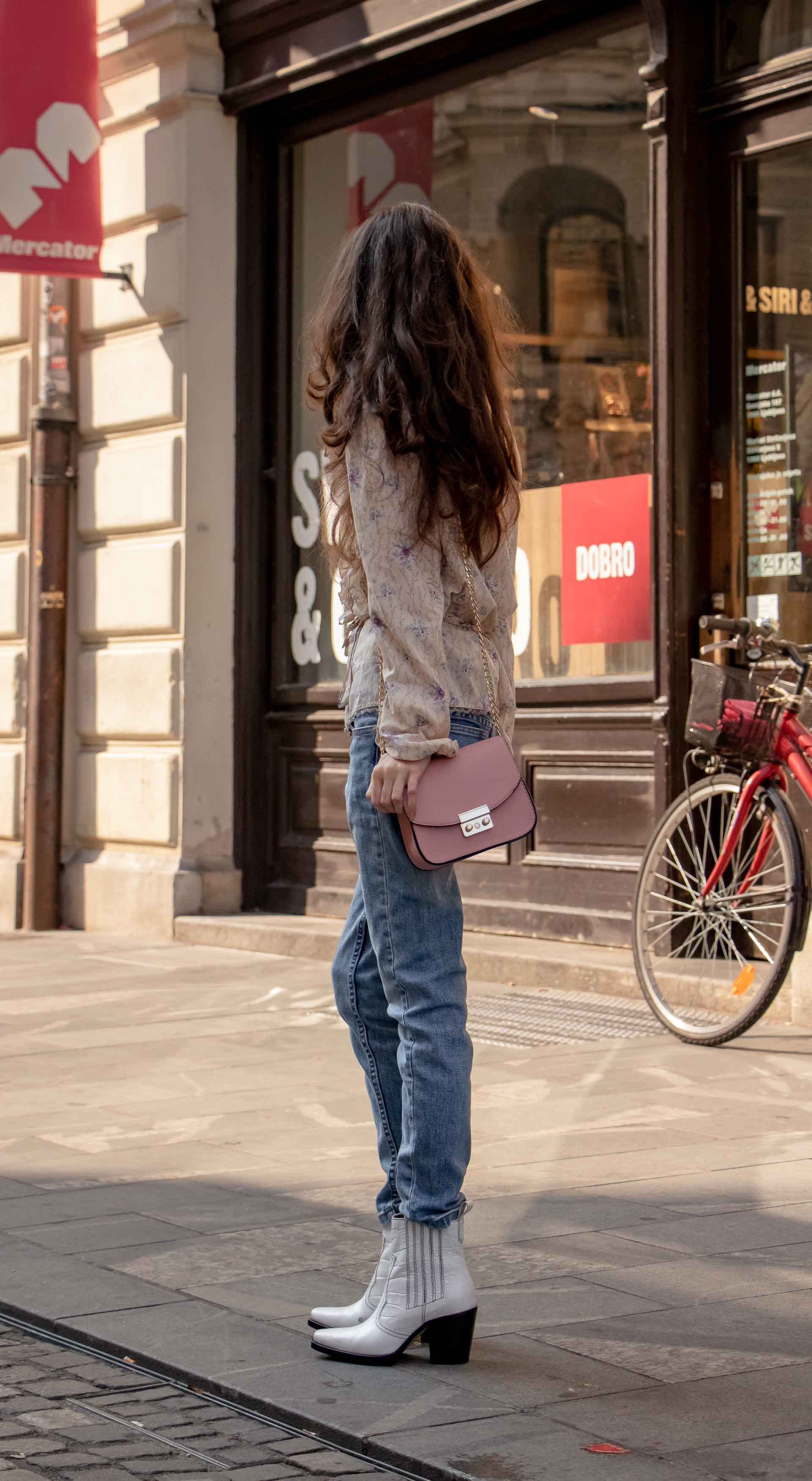 Beautiful Slovenian Fashion Blogger Veronika Lipar of Brunette from Wall wearing white Ganni Western boots, floral long sleeved Prairie blouse, A.P.C. blue jeans on the street in autumn in Ljubljana