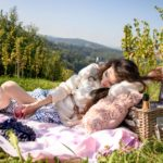 Beautiful Slovenian Fashion Blogger Veronika Lipar of Brunette from Wall wearing blue and white check button down Mango dress, oversized white turtleneck sweater, dangling belt, white Ganni cowboy boots, for fall picnic in vineyard