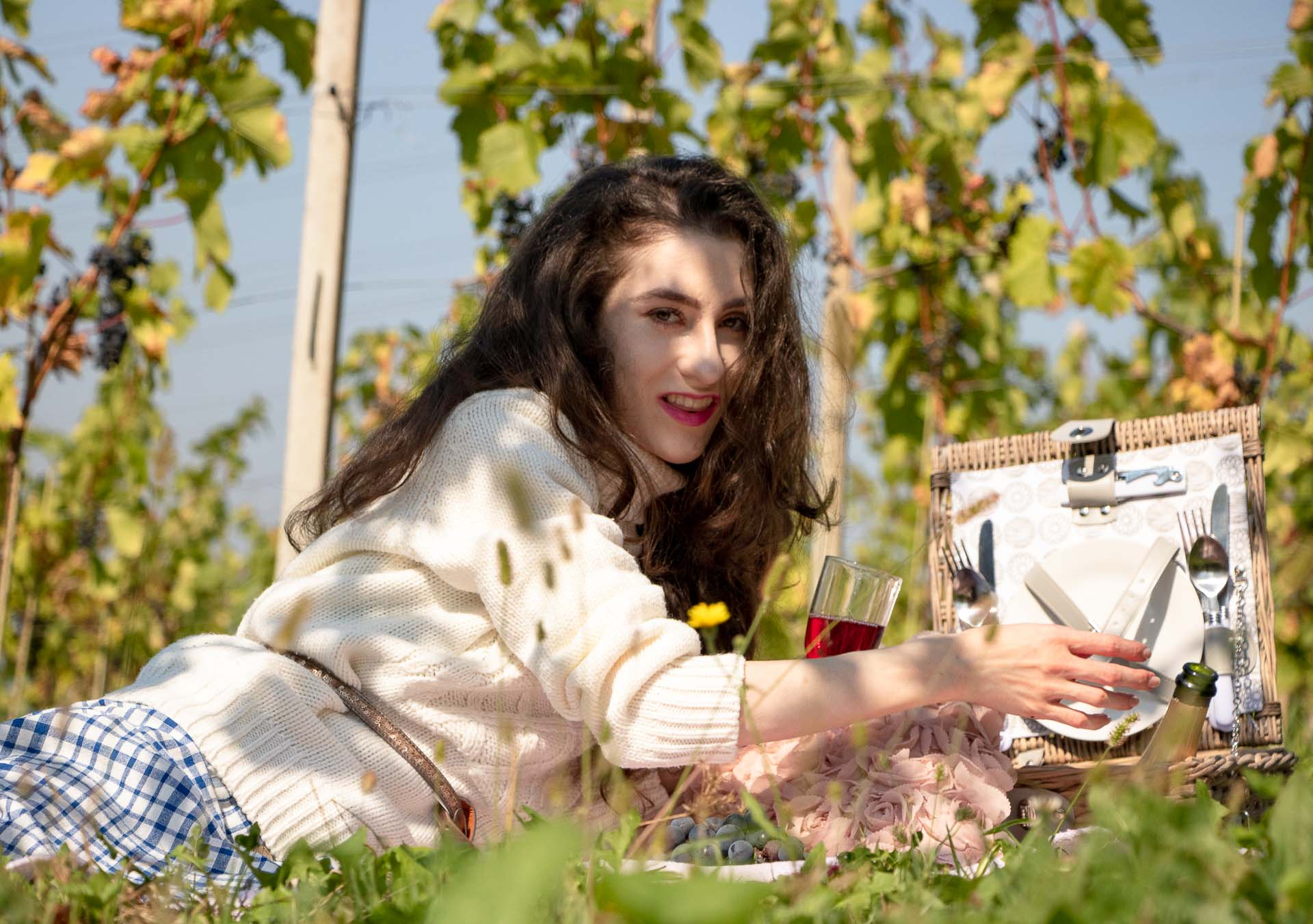 Beautiful Slovenian Fashion Blogger Veronika Lipar of Brunette from Wall Street dressed in blue and white check button down Mango dress, oversized white turtleneck sweater, dangling belt at the countryside picnic in vineyard