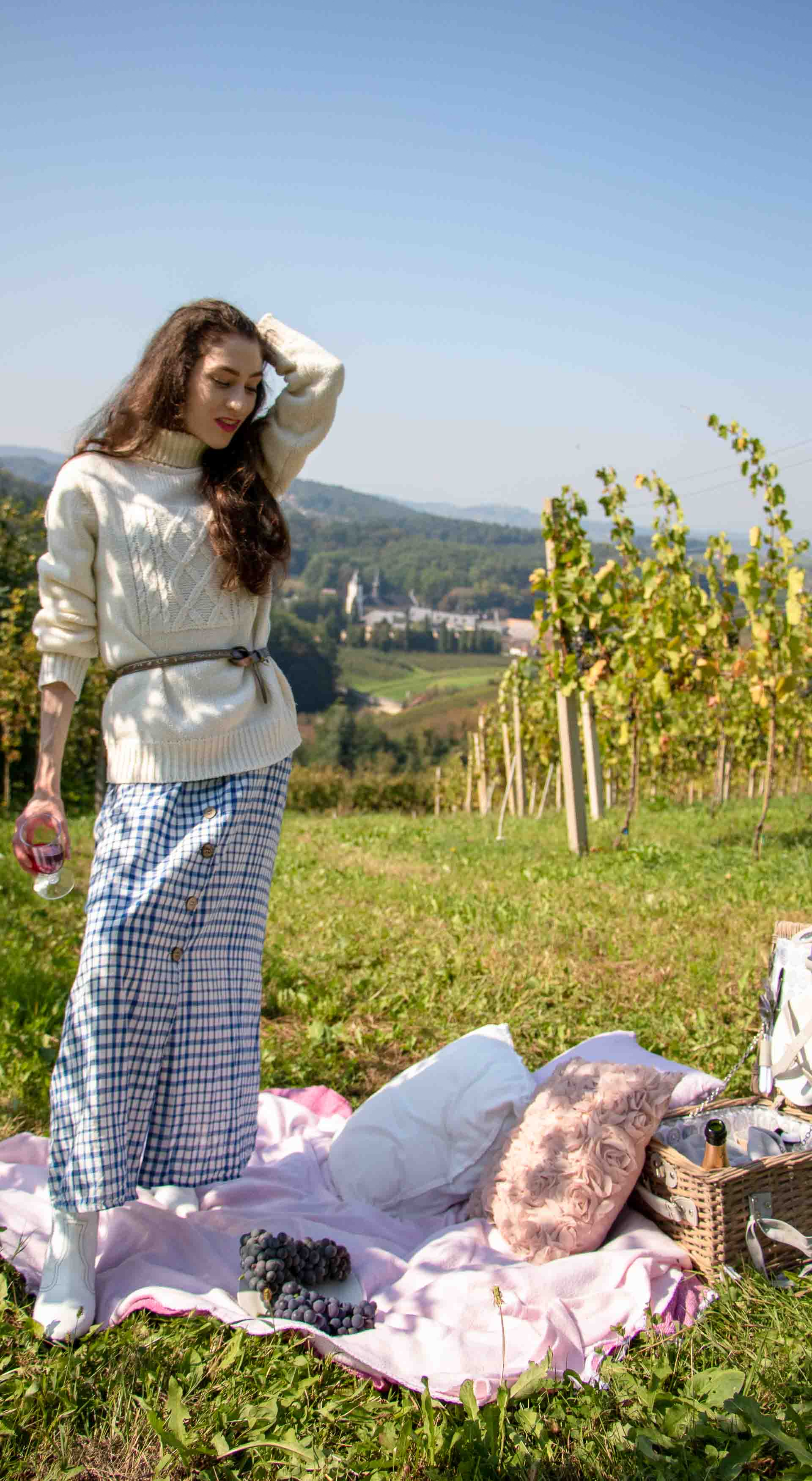Beautiful Slovenian blogger Veronika Lipar of Brunette from Wall street at fall picnic in vineyard wearing oversized sweater over button down check long dress