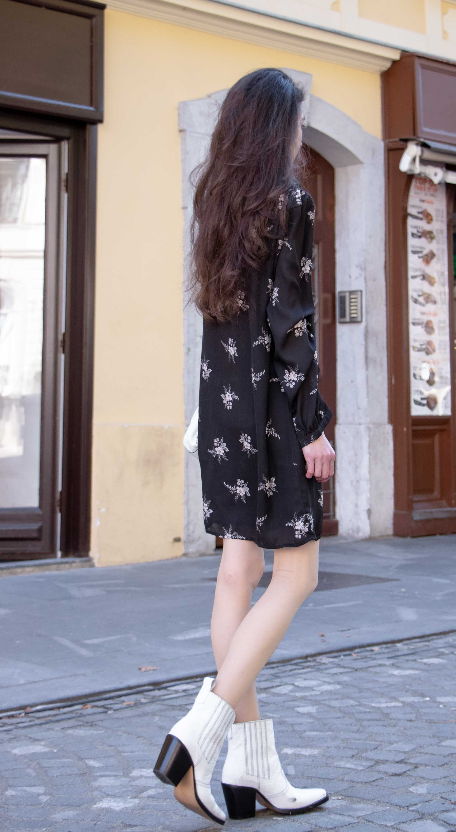 Beautiful Slovenian Fashion Blogger Veronika Lipar of Brunette from Wall wearing dark floral button down dress with white Ganni cowboy boots, white chain shoulder bag in autumn on the street in Ljubljana