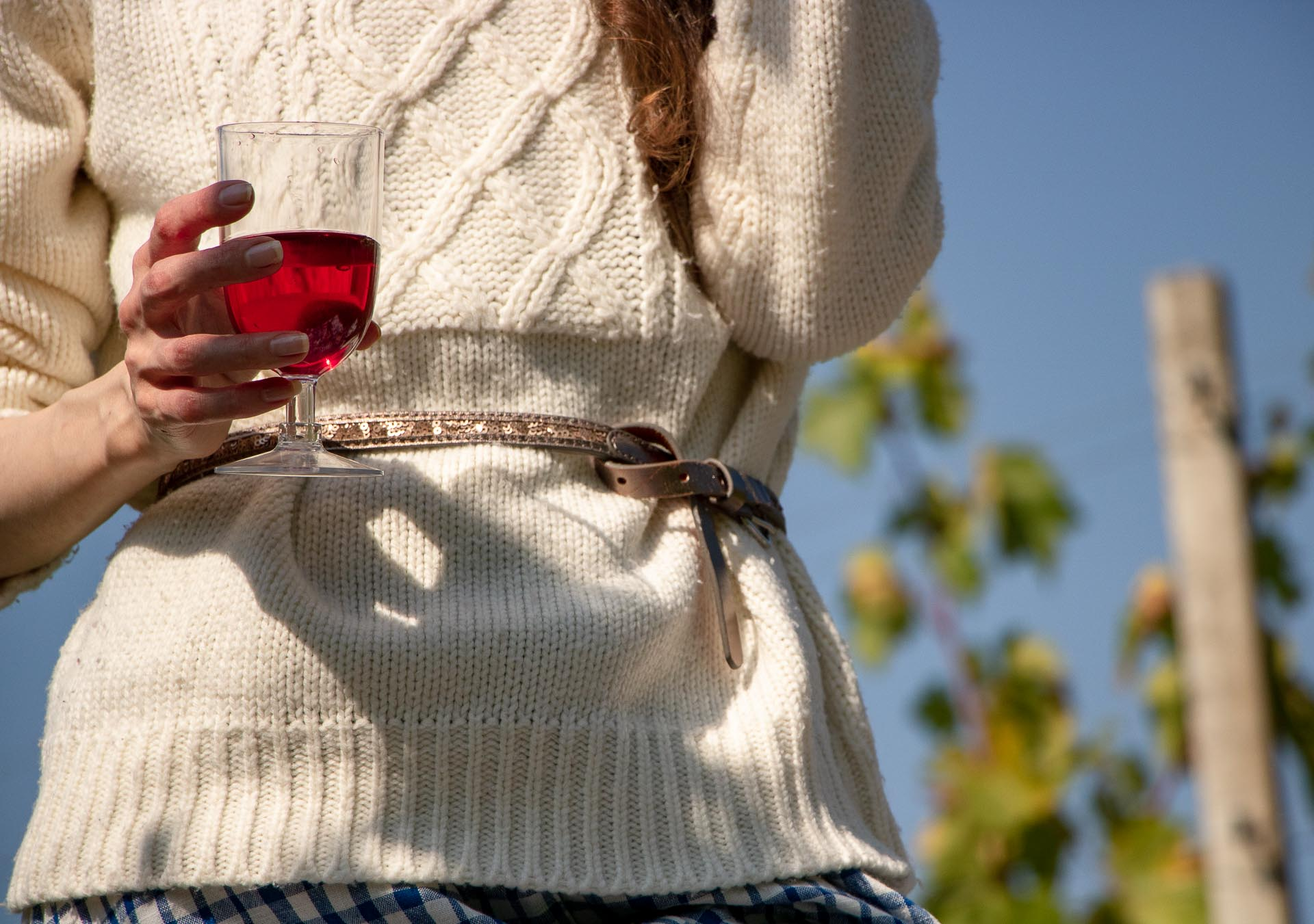 Beautiful Slovenian Fashion Blogger Veronika Lipar of Brunette from Wall Street dressed in blue and white check button down Mango dress, oversized white turtleneck sweater, dangling belt holding a red wine glass