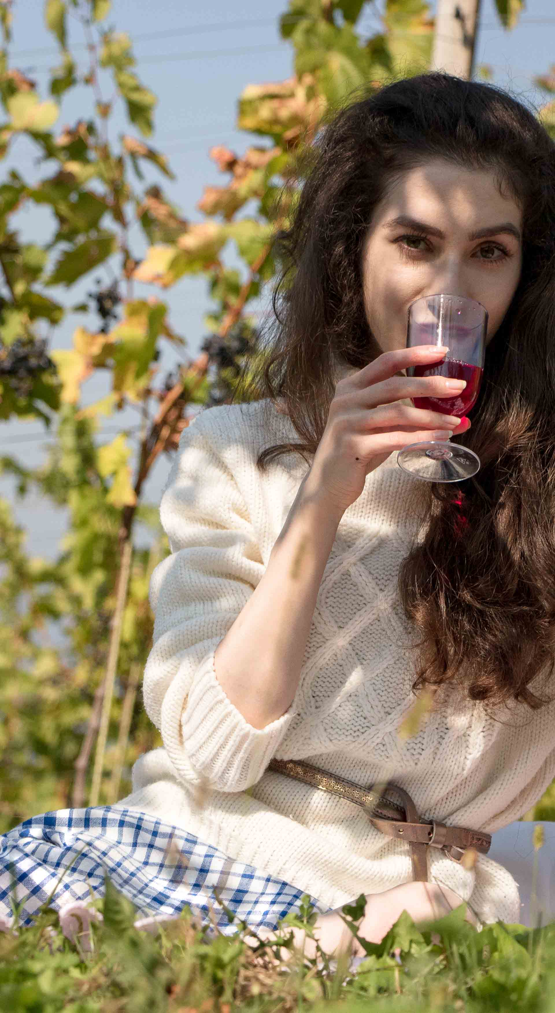 Beautiful Slovenian Fashion Blogger Veronika Lipar of Brunette from Wall dressed in blue and white check button down Mango dress, oversized white turtleneck sweater, dangling belt drinking wine