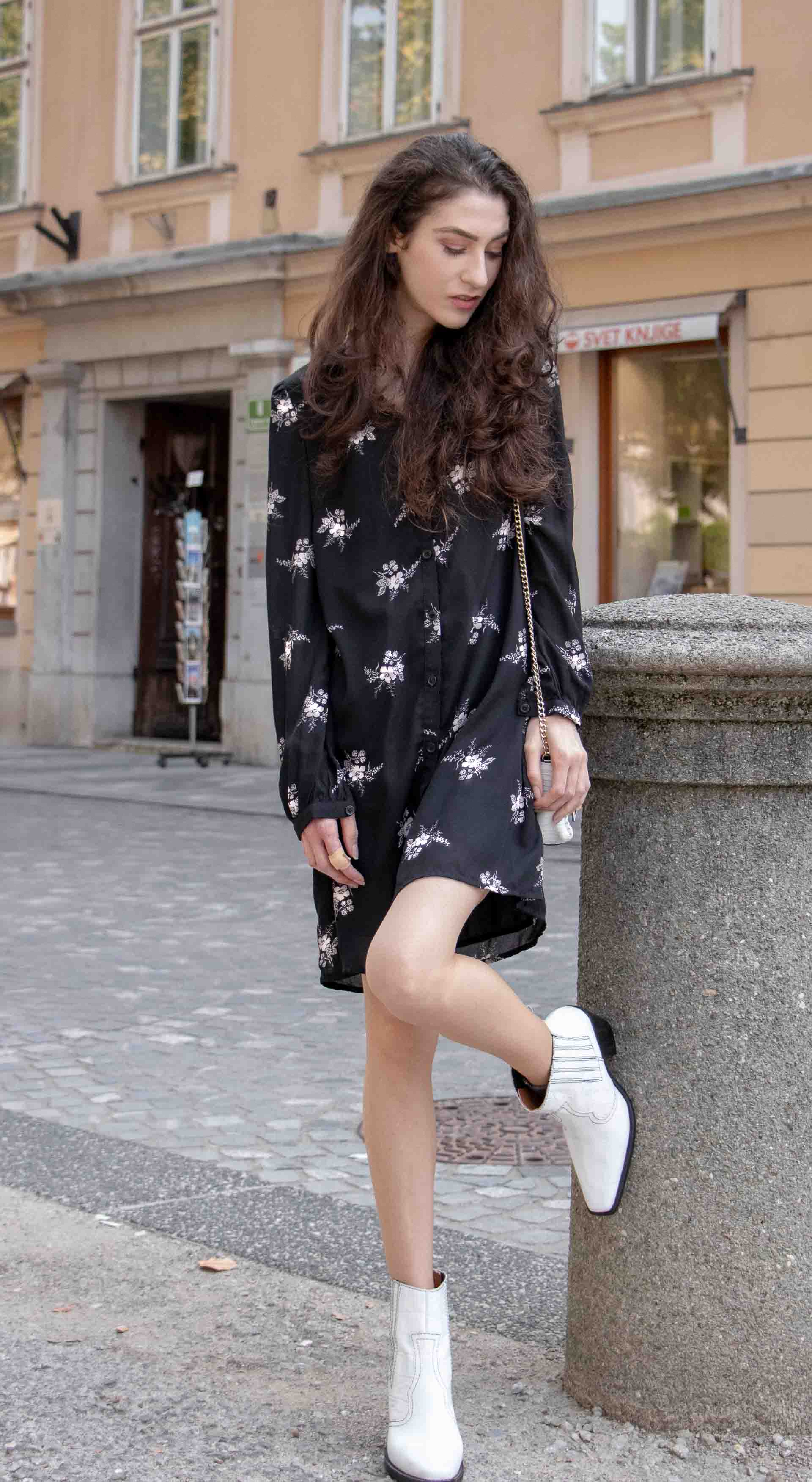 Beautiful Slovenian Fashion Blogger Veronika Lipar of Brunette from Wall dressed in dark floral shirtdress with white Ganni cowboy boots, white chain shoulder bag in Fall leaning on the wall
