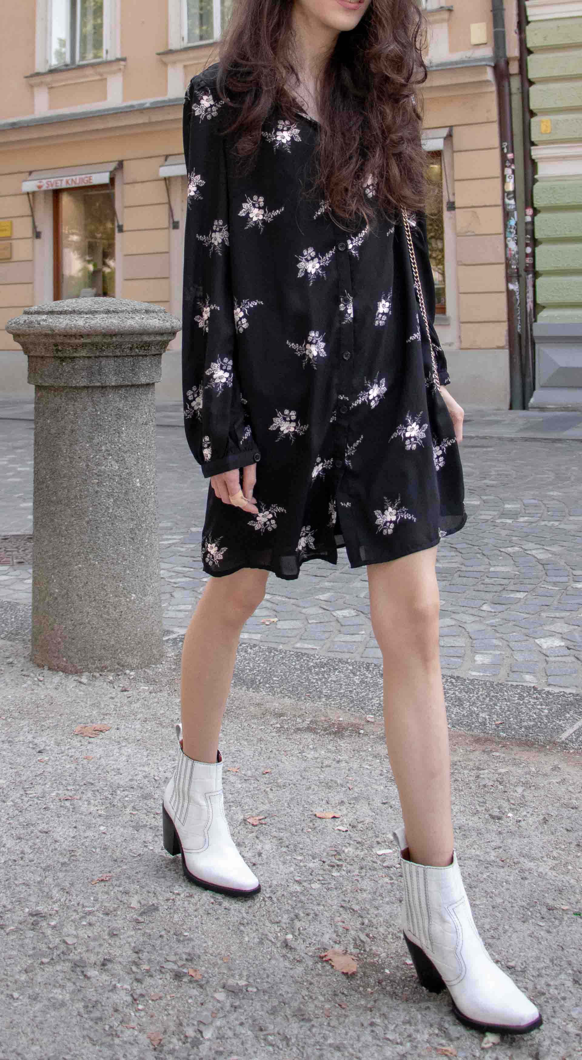 Beautiful Slovenian Fashion Blogger Veronika Lipar of Brunette from Wall wearing dark floral shirtdress with white Ganni cowboy boots, white chain shoulder bag in Fall on the street in Ljubljana