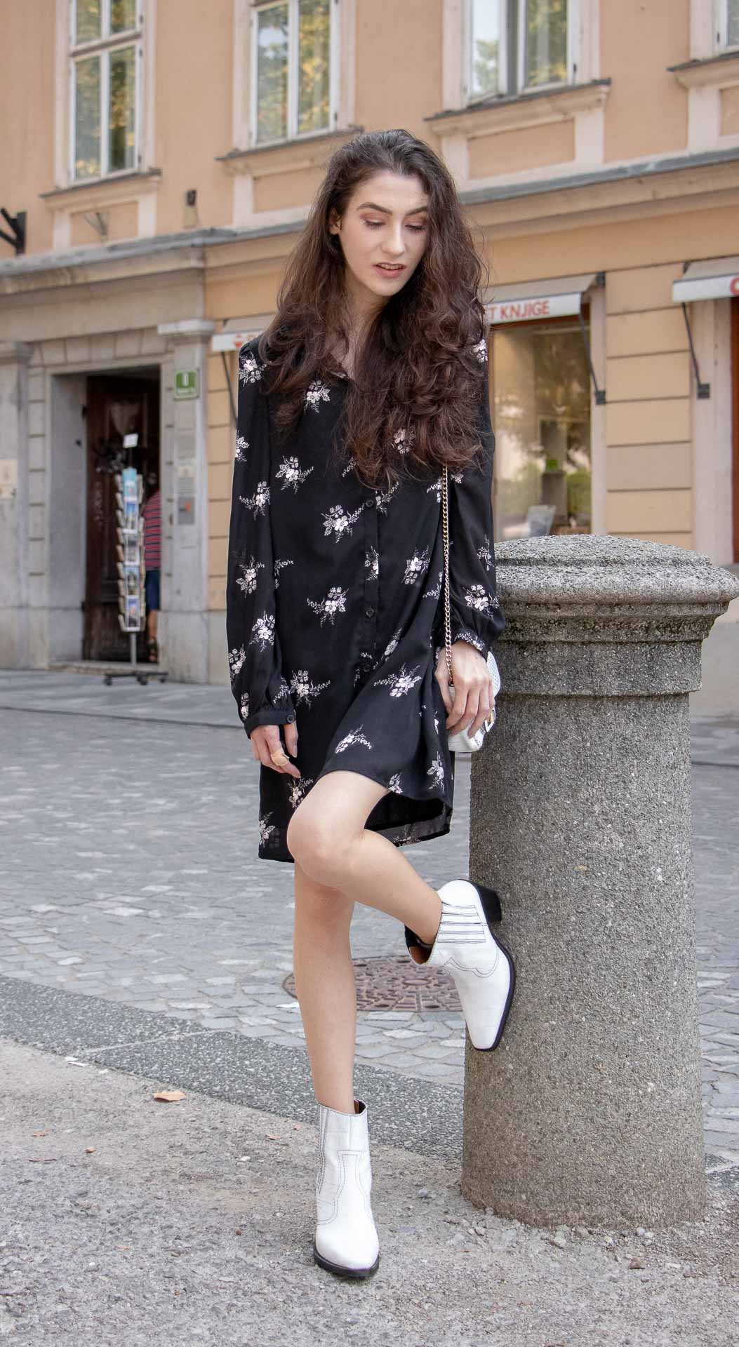Slovenska modna blogerka Slovenian Fashion Blogger Veronika Lipar of Brunette from Wall Street wearing black floral button down shirt dress, white shoulder bag, white Ganni boots on Friday leaning on the wall