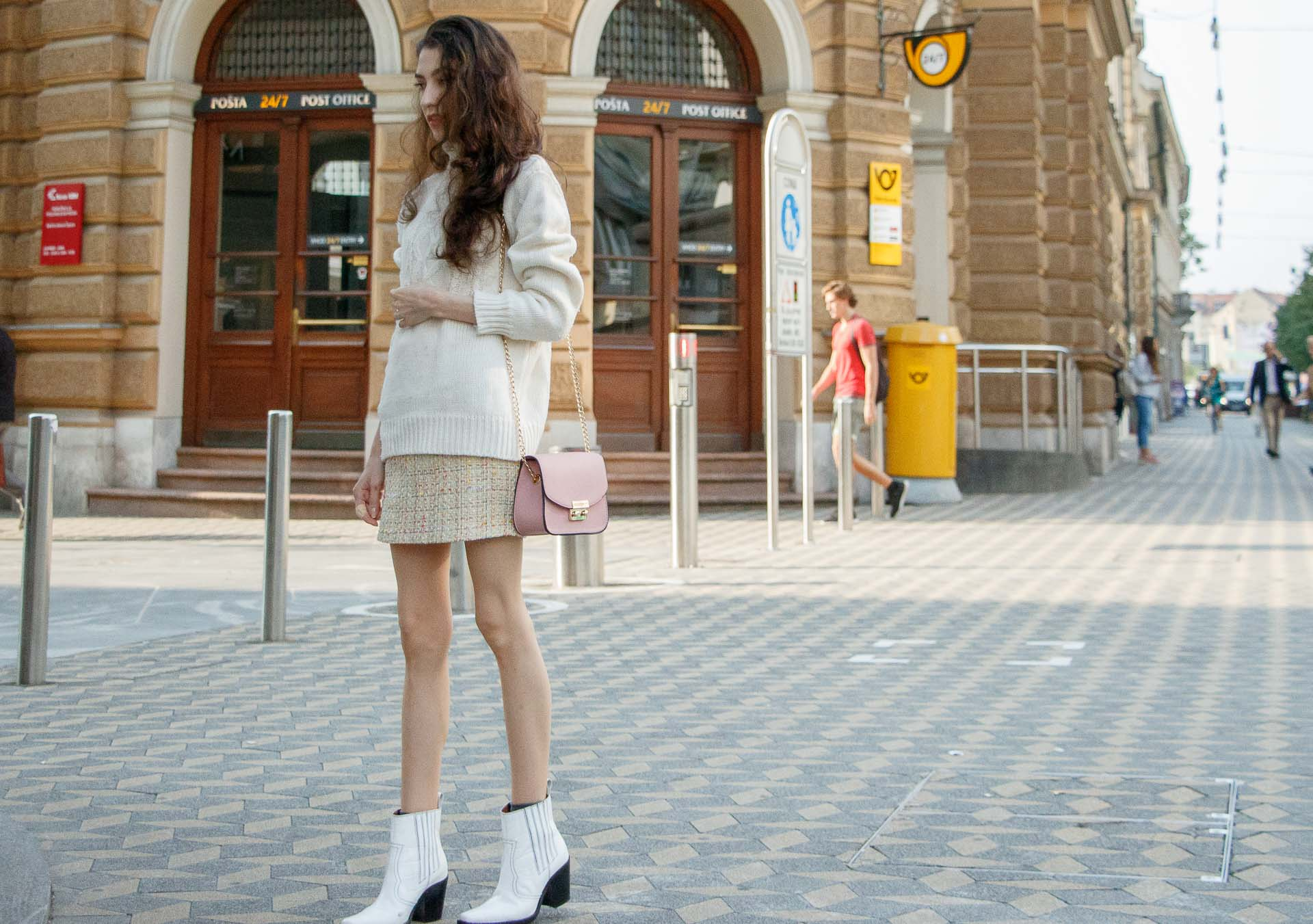 Beautiful Slovenian Fashion Blogger Veronika Lipar of Brunette from Wall wearing white Ganni Western boots, yellow tweed skirt, white turtleneck sweater, chain strap shoulder bag on the street in the morning in Ljubljana in autumn
