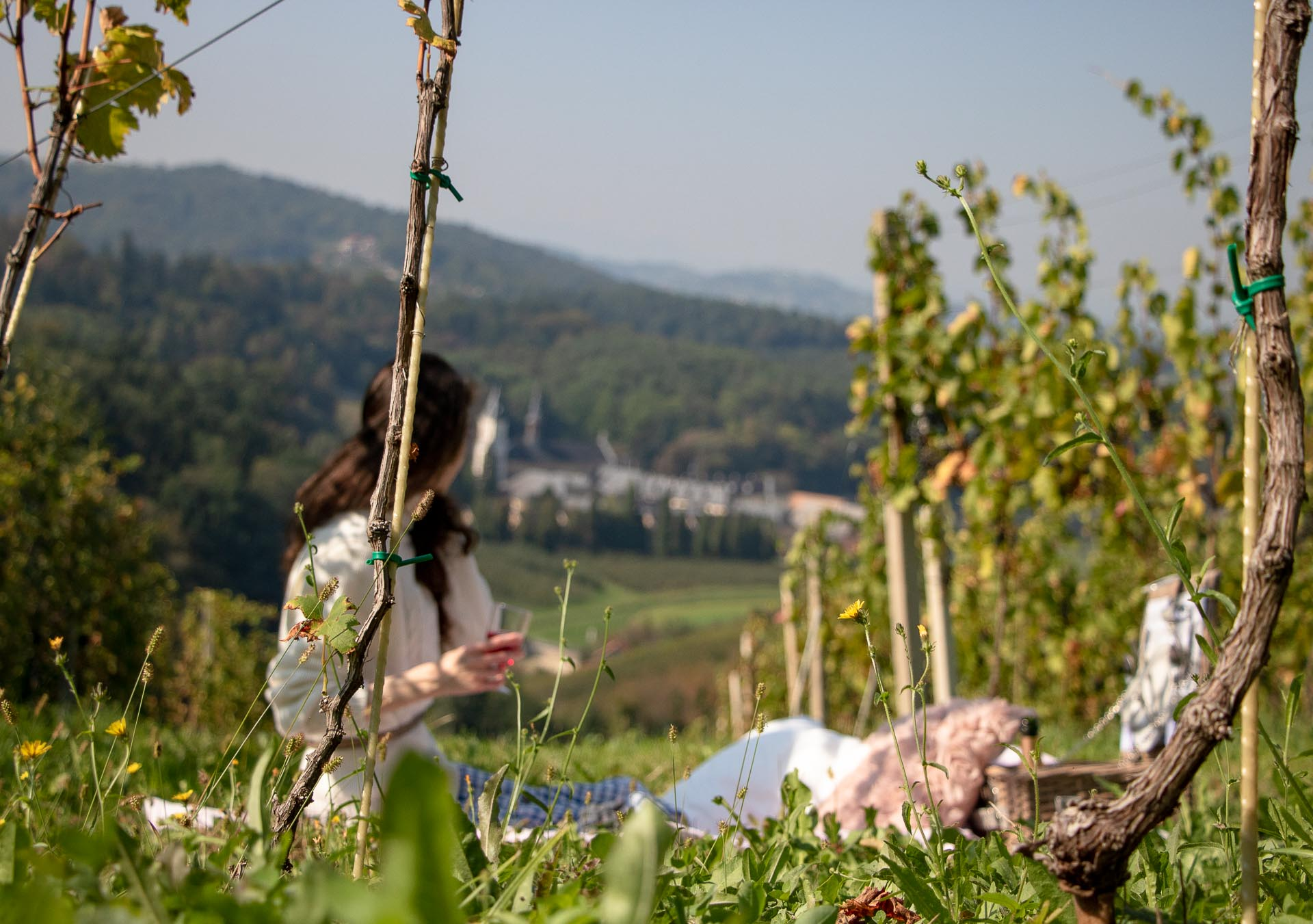 Beautiful Slovenian Fashion Blogger Veronika Lipar of Brunette from Wall dressed in blue and white check button down Mango dress, oversized white turtleneck sweater, dangling belt, white Ganni cowboy boots, for autumn picnic in vineyard