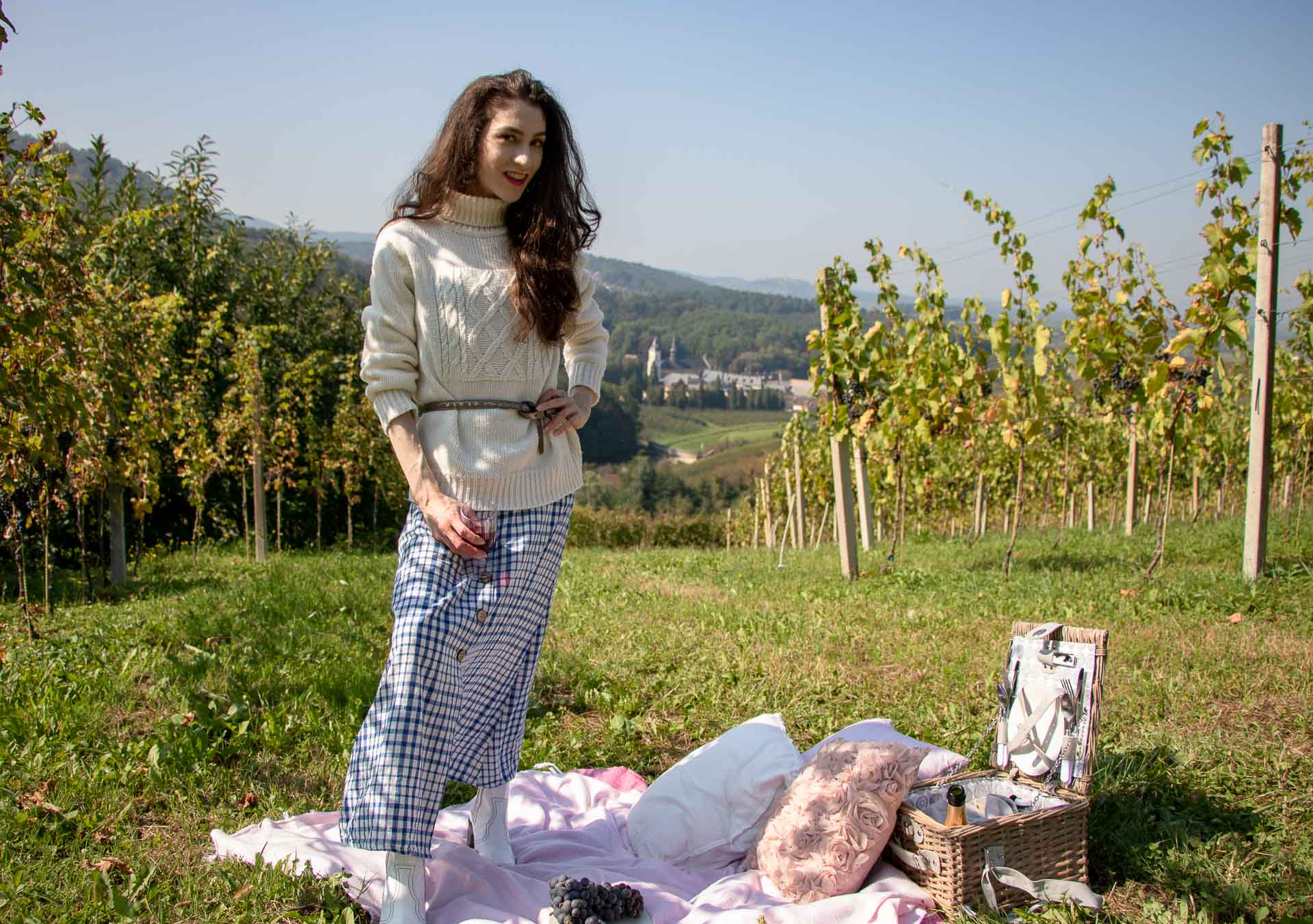 Beautiful Slovenian Fashion Blogger Veronika Lipar of Brunette from Wall Street wearing blue and white check button down Mango dress, oversized white turtleneck sweater, dangling belt, white Ganni cowboy boots, for autumn picnic in countryside