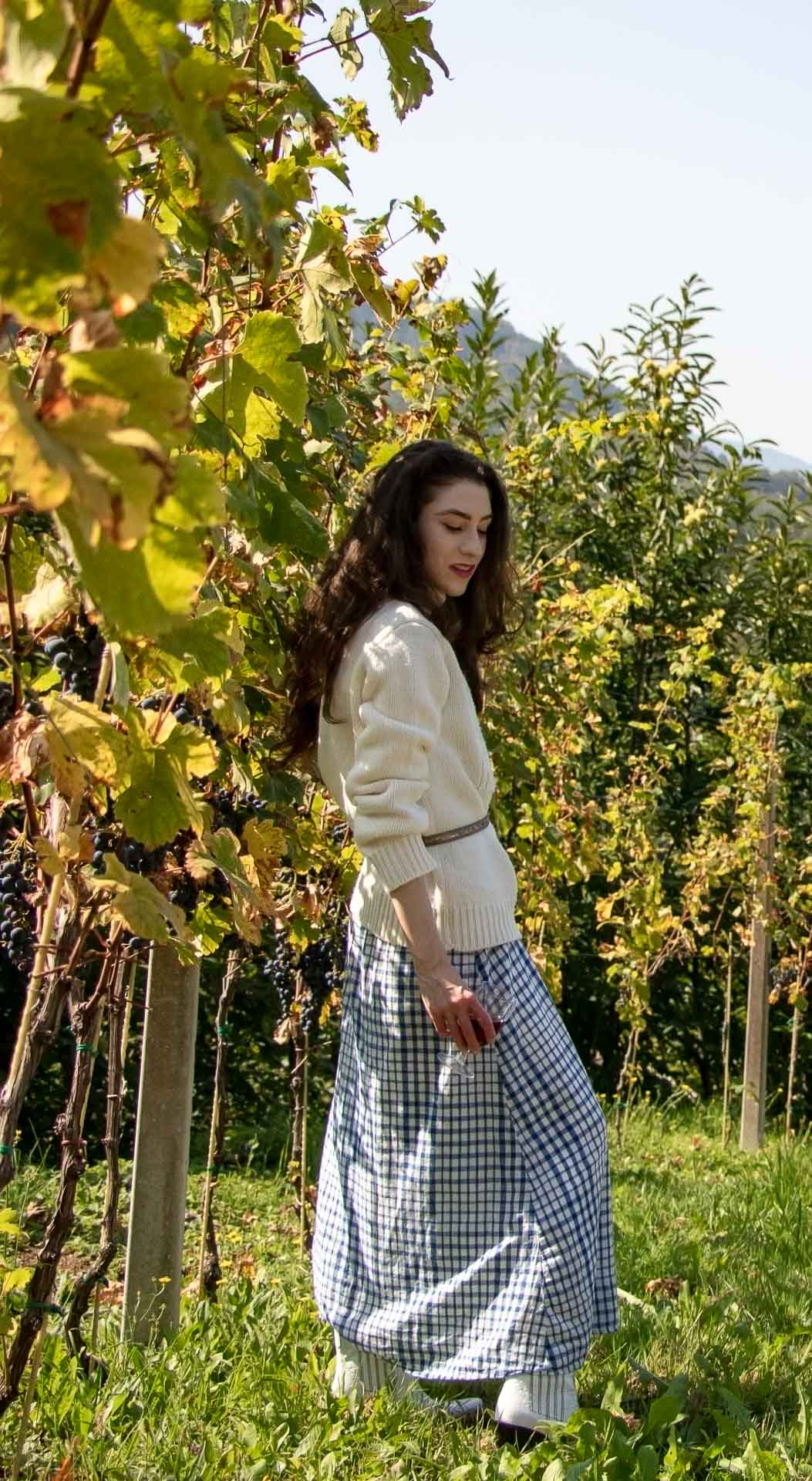 Beautiful Slovenian Fashion Blogger Veronika Lipar of Brunette from Wall dressed in blue and white check button down Mango dress, oversized white turtleneck sweater, dangling belt, white Ganni cowboy boots, for fall picnic in countryside