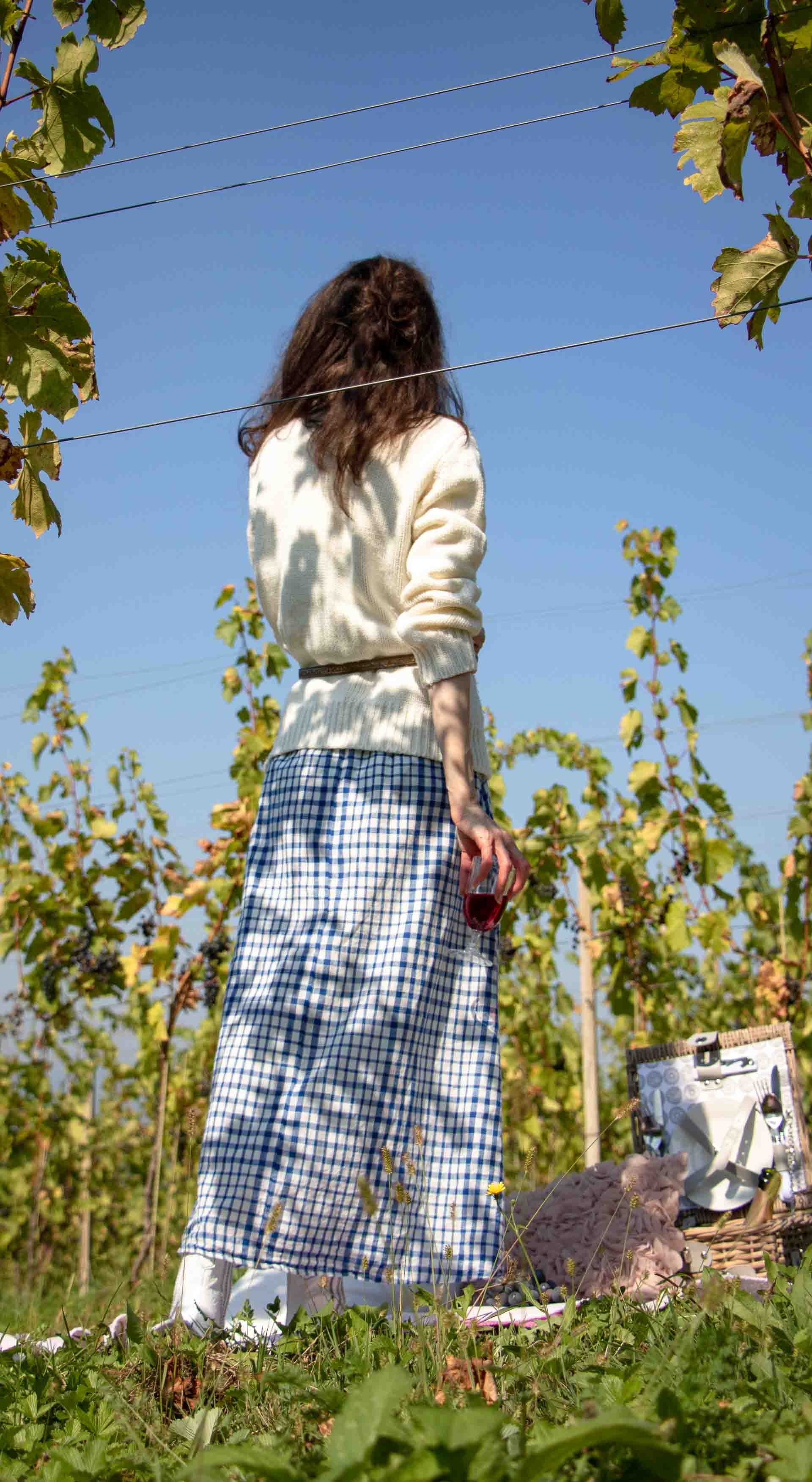 Beautiful Slovenian Fashion Blogger Veronika Lipar of Brunette from Wall dressed in blue and white check button down Mango dress, oversized white turtleneck sweater, dangling belt, white Ganni cowboy boots, for autumn picnic in countryside