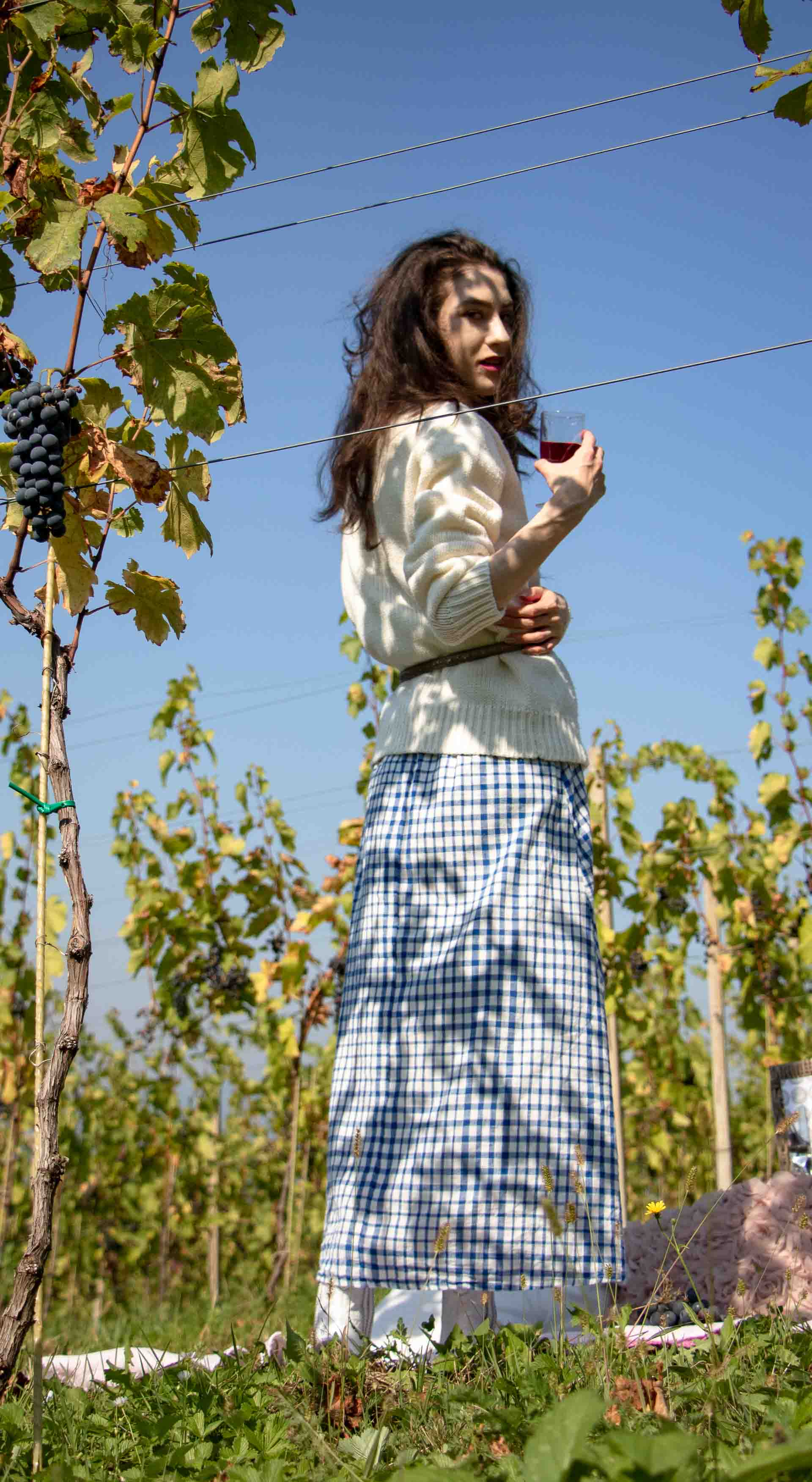 Beautiful Slovenian Fashion Blogger Veronika Lipar of Brunette from Wall dressed in blue and white check button down Mango dress, oversized white turtleneck sweater, dangling belt, white Ganni cowboy boots, for fall picnic in vineyard