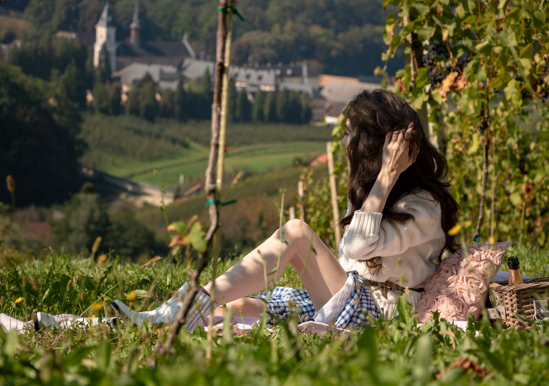 Beautiful Slovenian Fashion Blogger Veronika Lipar of Brunette from Wall Street dressed in blue and white check button down Mango dress, oversized white turtleneck sweater, dangling belt, white Ganni cowboy boots, for fall picnic in vineyard