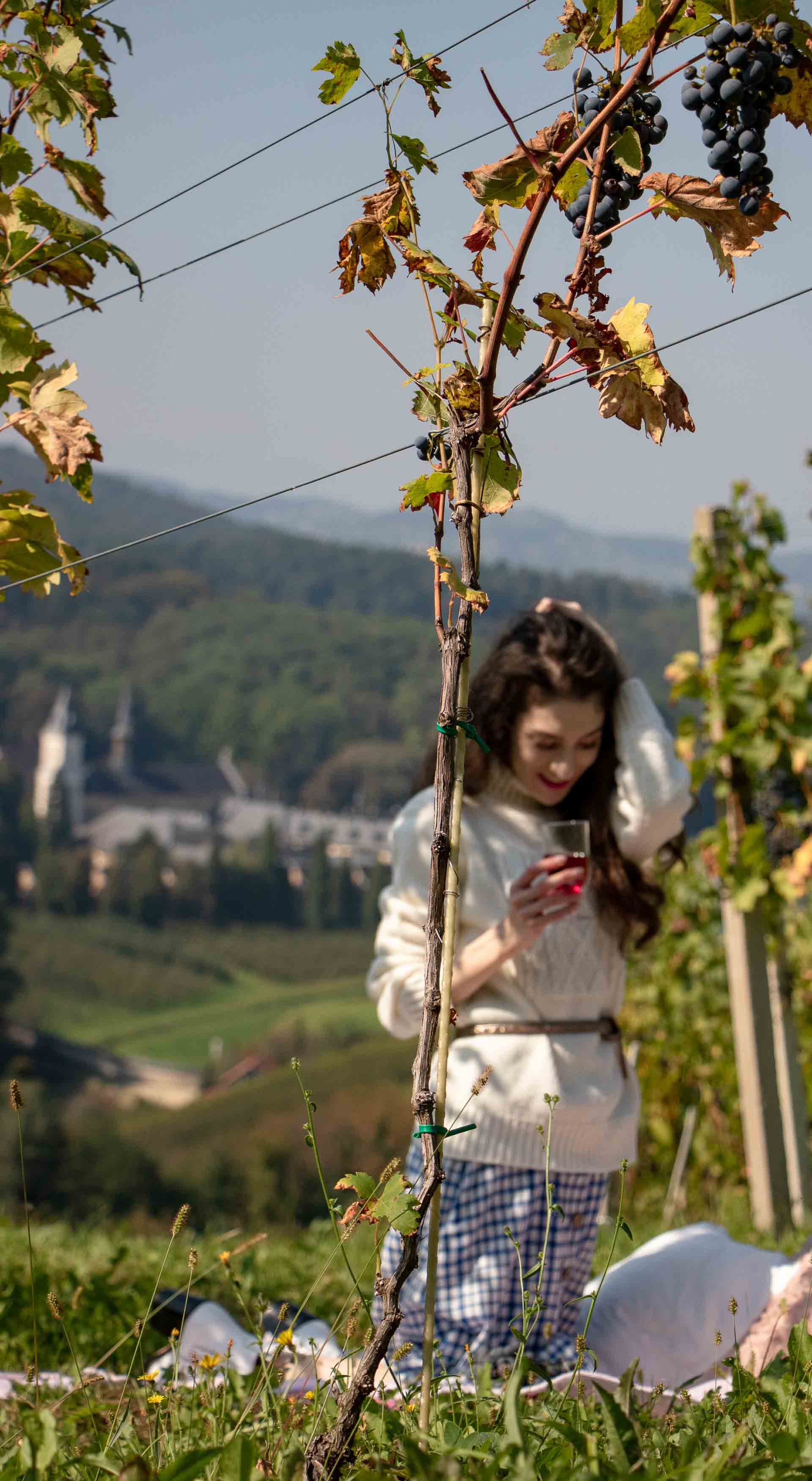 Beautiful Slovenian Fashion Blogger Veronika Lipar of Brunette from Wall Street dressed in blue and white check button down Mango dress, oversized white turtleneck sweater, dangling belt for autumn picnic in vineyard