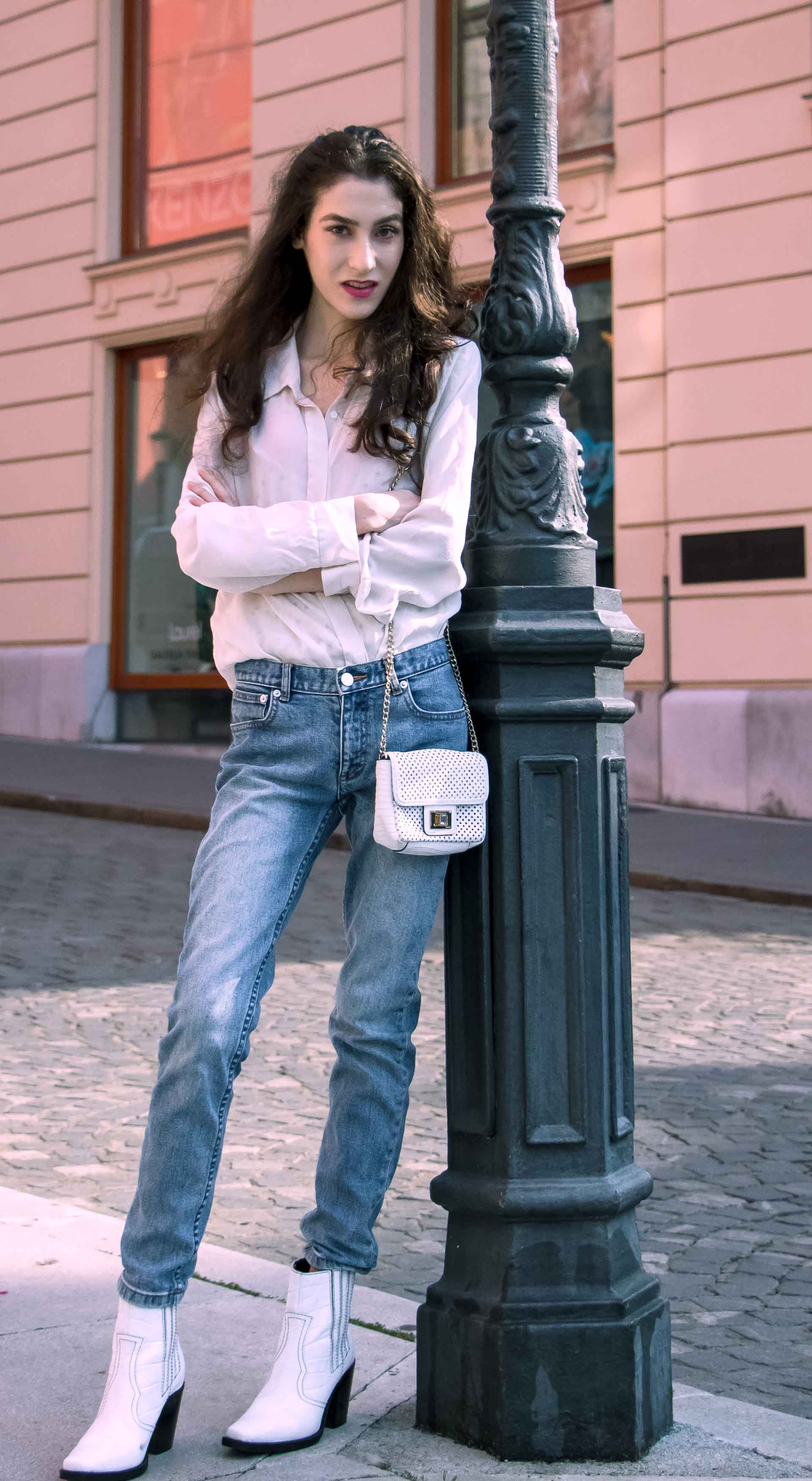 Beautiful Slovenian Fashion Blogger Veronika Lipar of Brunette from Wall dressed in white silk shirt from Sandro Paris, white and black polka dot cami slip top, A.P.C. light blue jeans, white Ganni Western boots, chain strap shoulder bag leaning on the street lamp