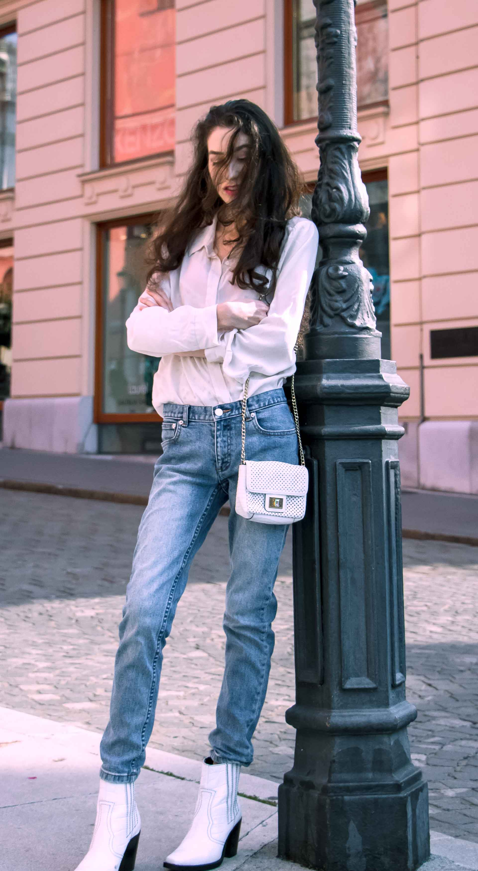 Beautiful Slovenian Fashion Blogger Veronika Lipar of Brunette from Wall wearing white silk shirt from Sandro Paris, white and black polka dot cami slip top, A.P.C. light blue jeans, white Ganni Western boots, chain strap shoulder bag leaning on the street lamp