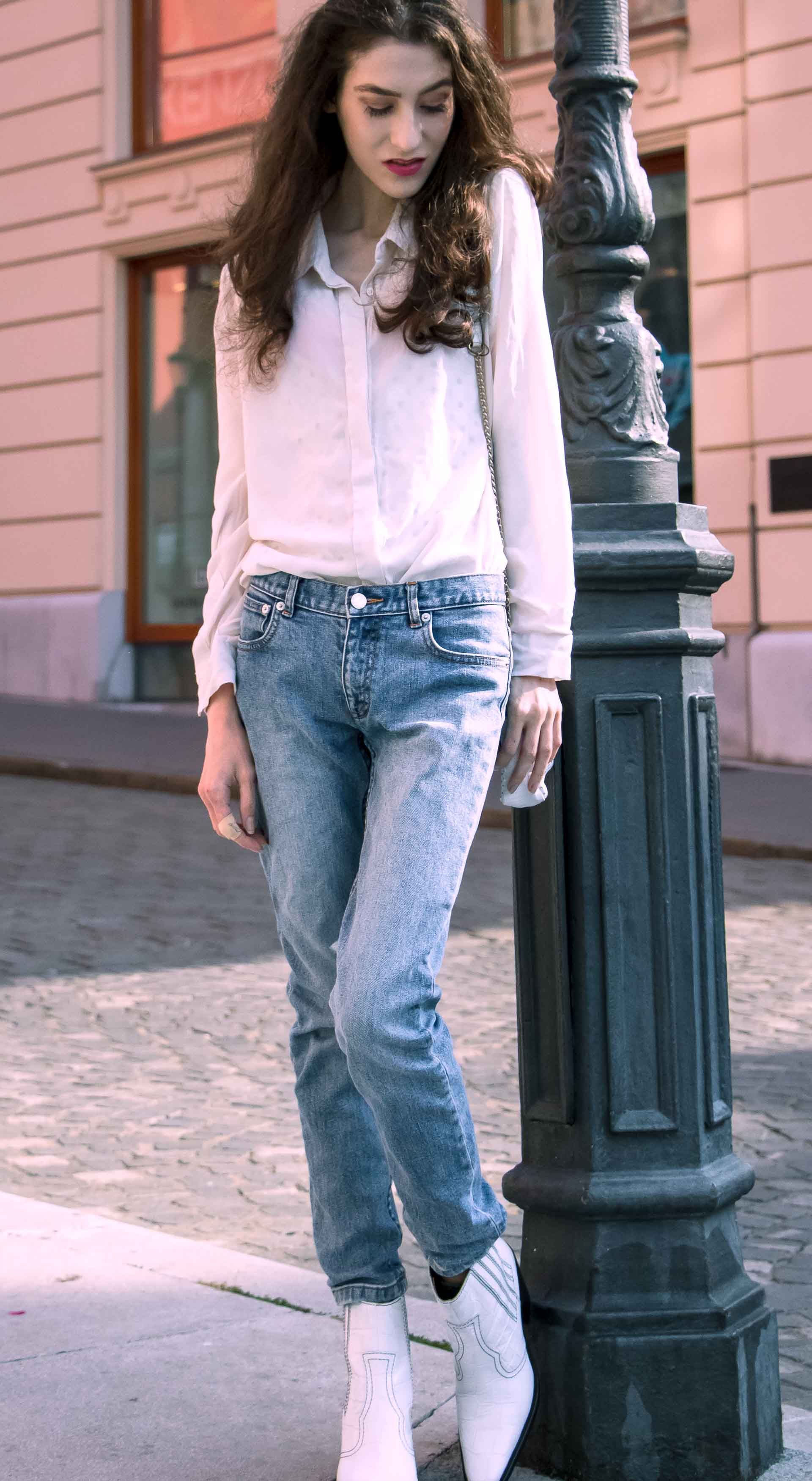 Beautiful Slovenian Fashion Blogger Veronika Lipar of Brunette from Wall wearing white silk shirt from Sandro Paris, white and black polka dot cami slip top, A.P.C. light blue jeans, white Ganni Western boots, chain strap shoulder bag standing by the street lamp