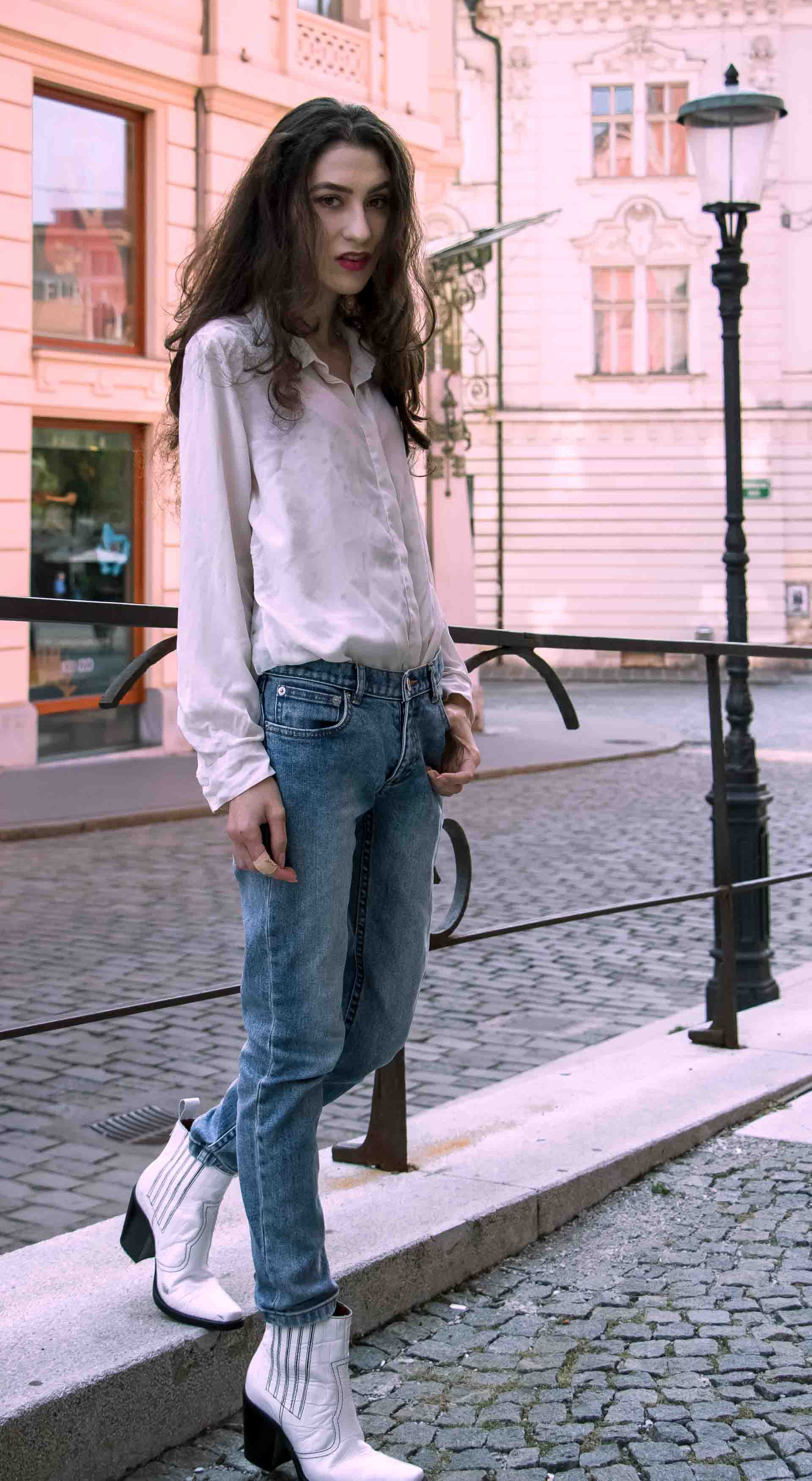 Beautiful Slovenian Fashion Blogger Veronika Lipar of Brunette from Wall dressed in white silk shirt from Sandro Paris, white and black polka dot cami slip top, A.P.C. light blue jeans, white Ganni Western boots, chain strap shoulder bag walking on the street