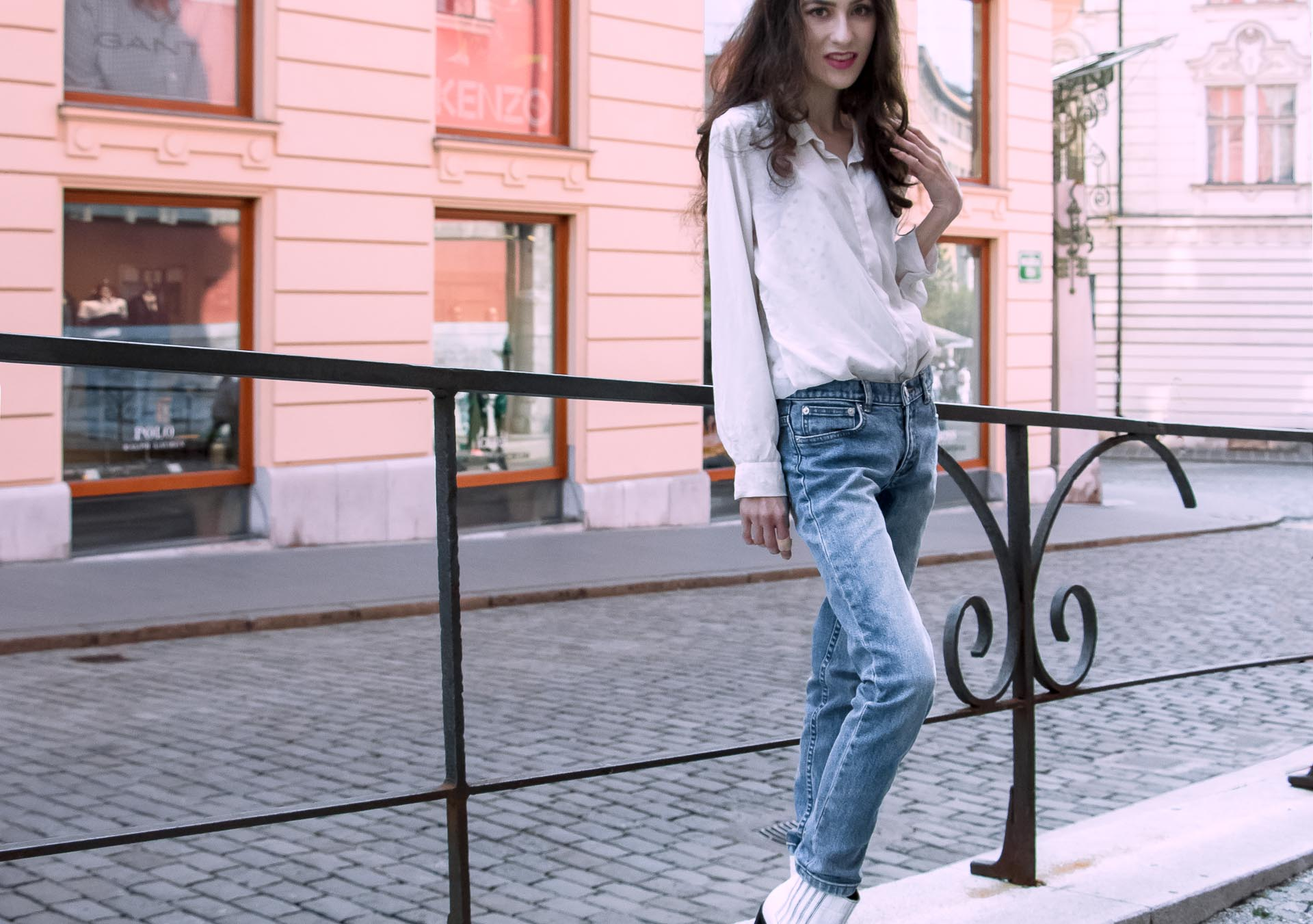 Beautiful Slovenian Fashion Blogger Veronika Lipar of Brunette from Wall wearing white silk shirt from Sandro Paris, white and black polka dot cami slip top, A.P.C. light blue jeans, white Ganni Western boots, chain strap shoulder bag standing on the street