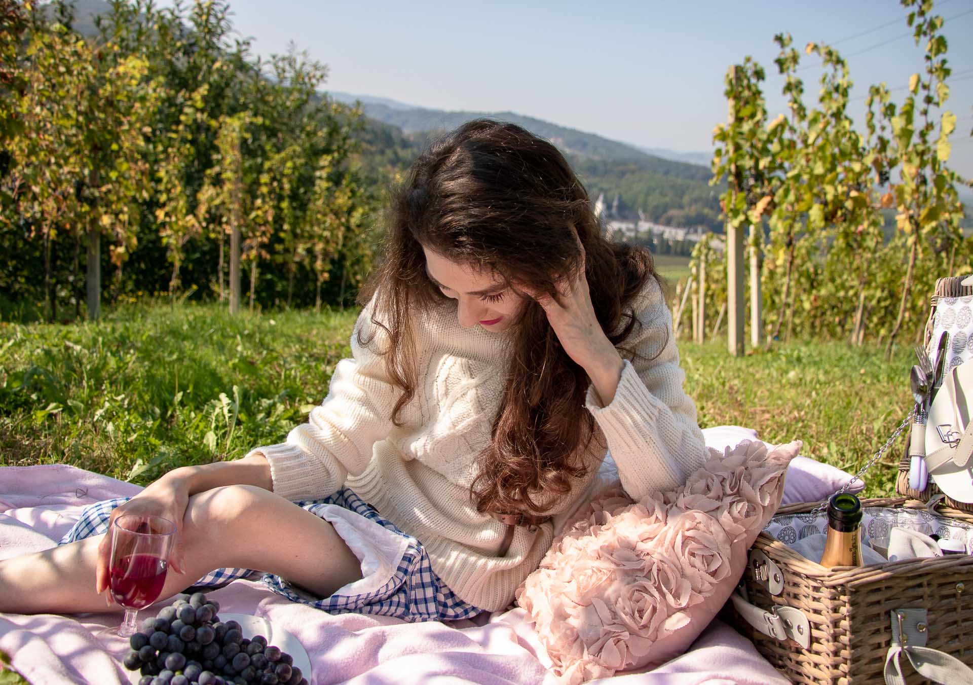 Beautiful Slovenian Fashion Blogger Veronika Lipar of Brunette from Wall Street wearing blue and white check button down Mango dress, oversized white turtleneck sweater, dangling belt, sitting on a picnic blanket in vineyard