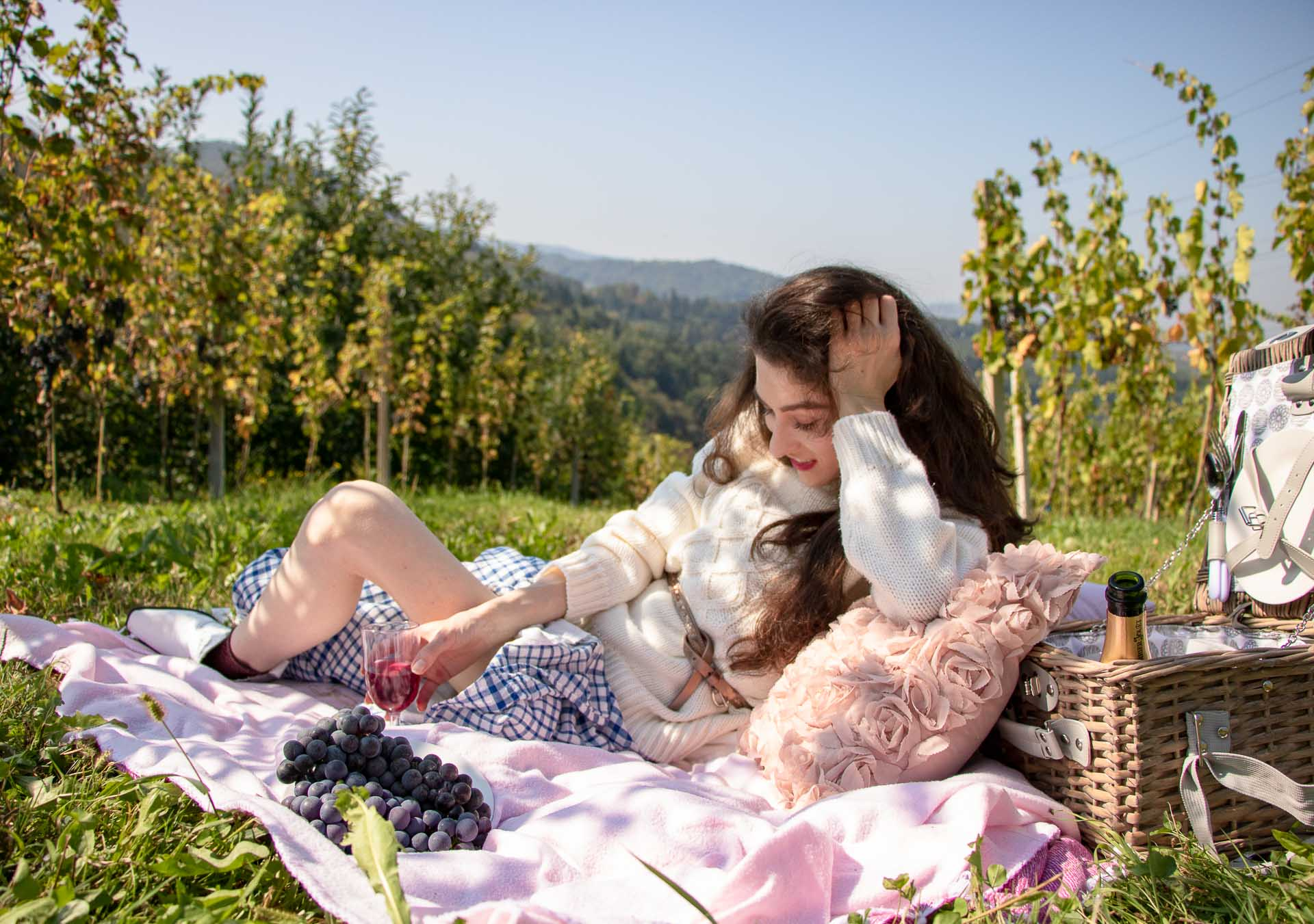 Beautiful Slovenian Fashion Blogger Veronika Lipar of Brunette from Wall dressed in blue and white check button down Mango dress, oversized white turtleneck sweater, dangling belt drinking wine, white Ganni cowboy boots, for fall picnic in vineyard