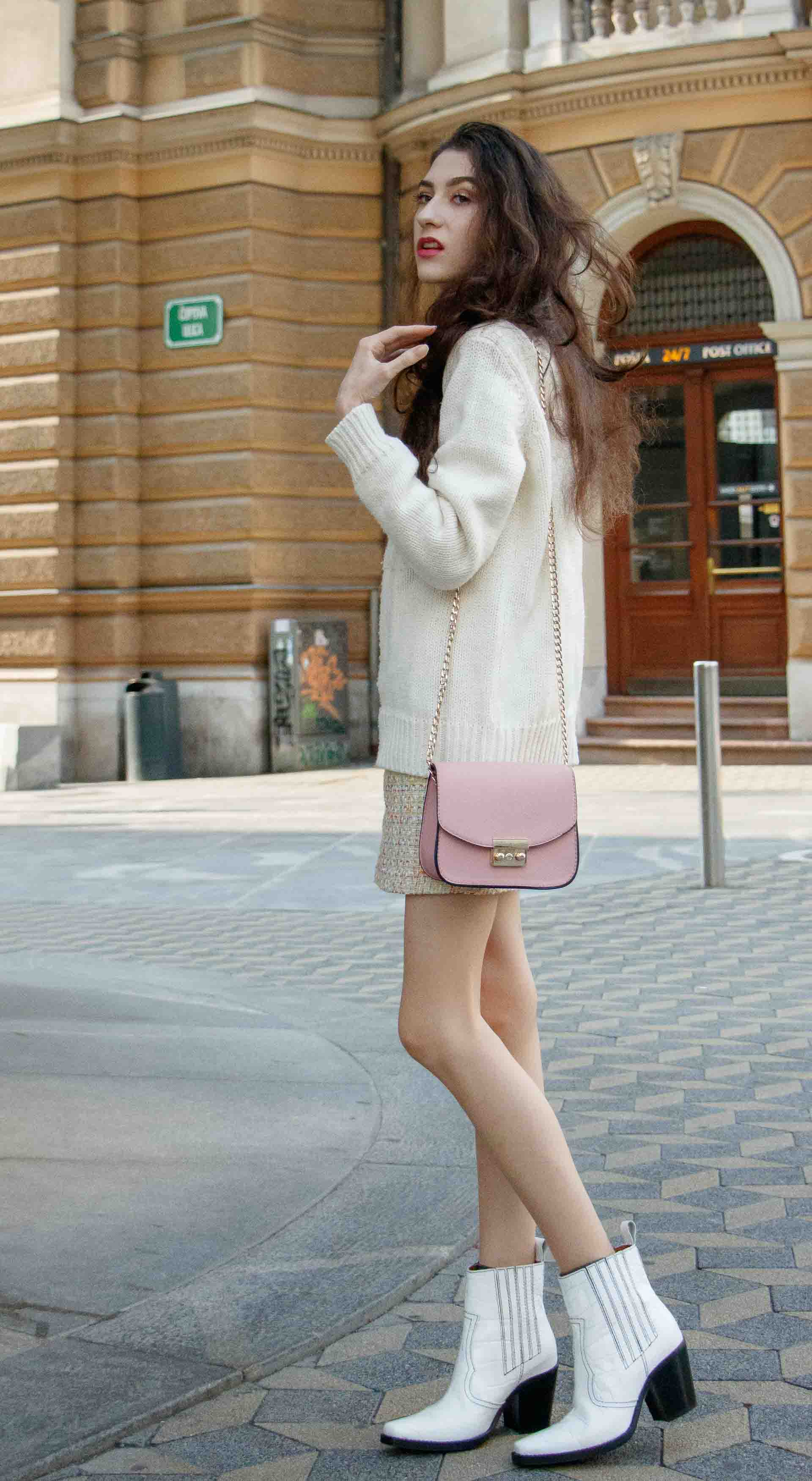 Beautiful Slovenian Fashion Blogger Veronika Lipar of Brunette from Wall dressed in white Ganni Western boots, yellow tweed skirt, white turtleneck sweater, chain strap shoulder bag on the street in the morning in Ljubljana in fall