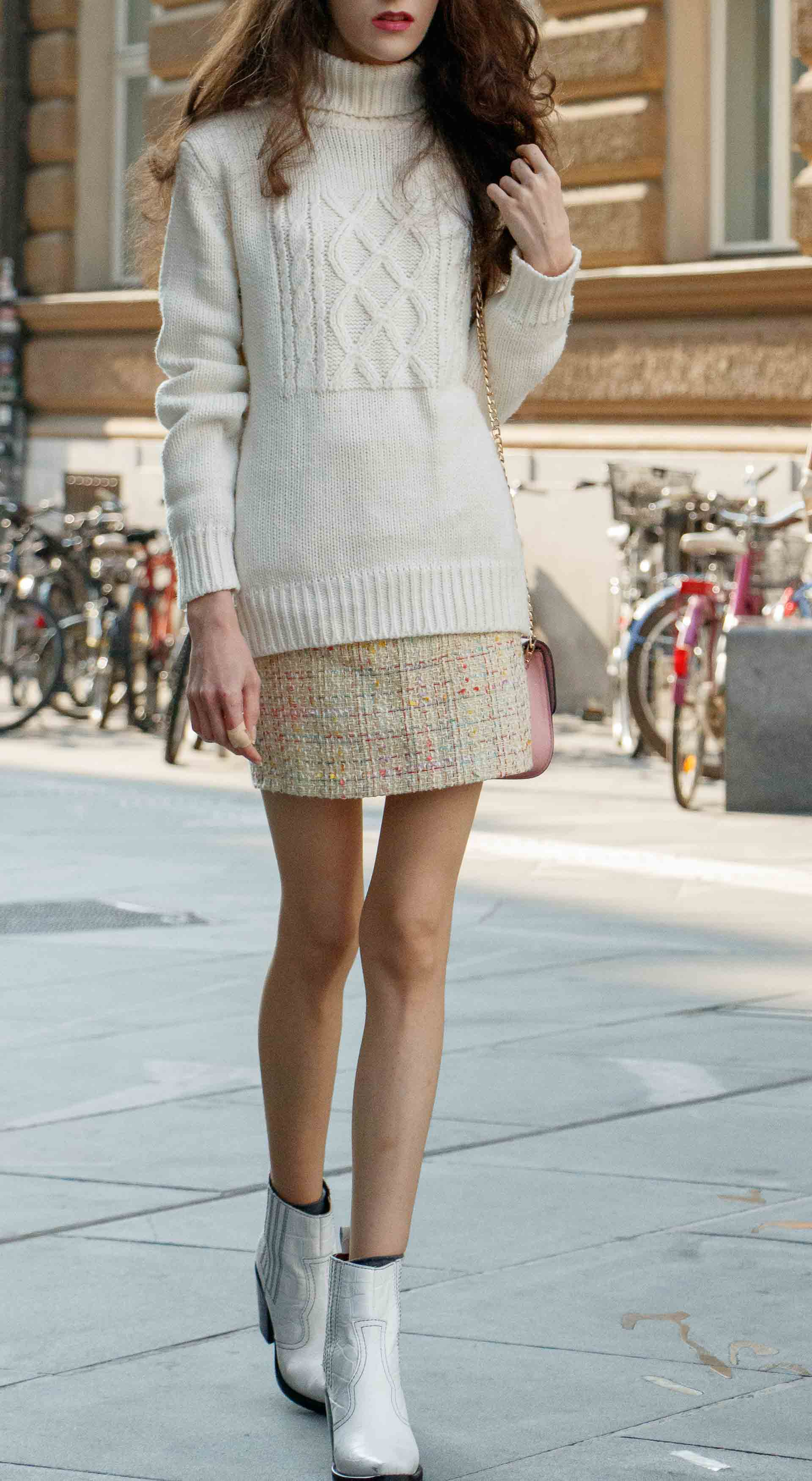 Beautiful Slovenian Fashion Blogger Veronika Lipar of Brunette from Wall dressed in white Ganni Western boots, yellow tweed skirt, white turtleneck sweater, chain strap shoulder bag walking on the street in the morning in Ljubljana in fall
