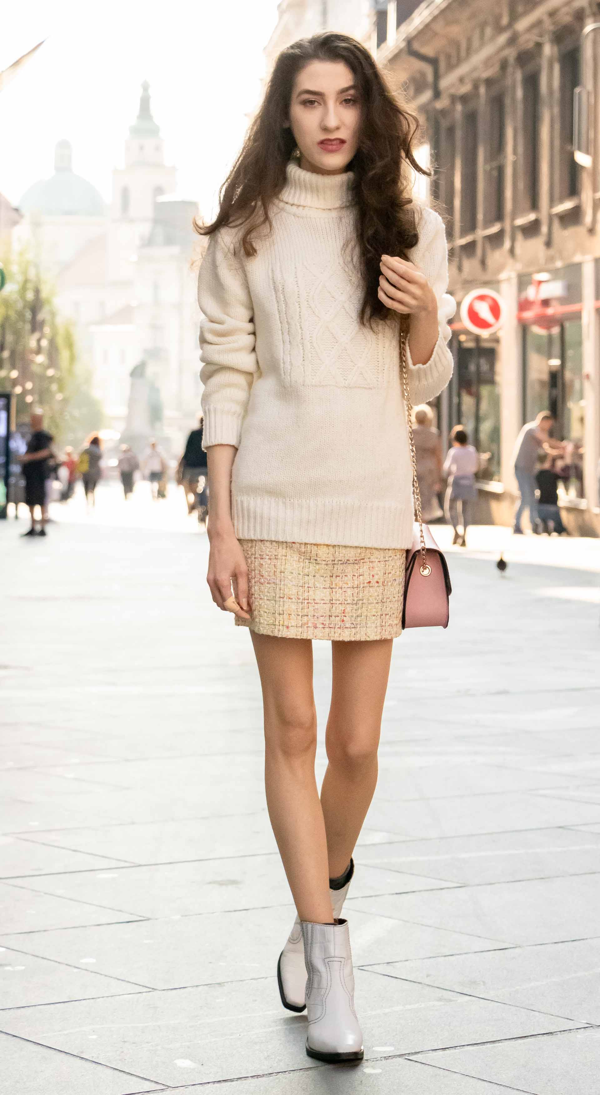 Beautiful Slovenian Fashion Blogger Veronika Lipar of Brunette from Wall wearing white Ganni Western boots, yellow tweed skirt, white turtleneck sweater, chain strap shoulder bag walking on the street in the morning in Ljubljana in fall