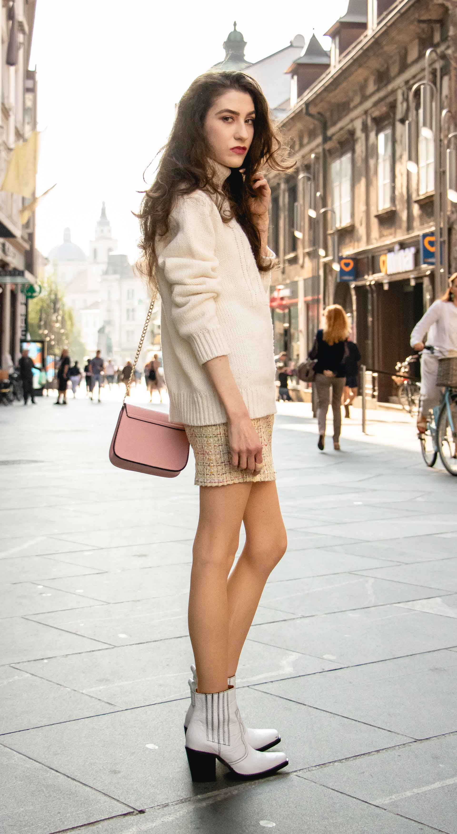 Beautiful Slovenian Fashion Blogger Veronika Lipar of Brunette from Wall dressed in white Ganni Western boots, yellow tweed skirt, white turtleneck sweater, chain strap shoulder bag standing on the street in the morning in Ljubljana in fall