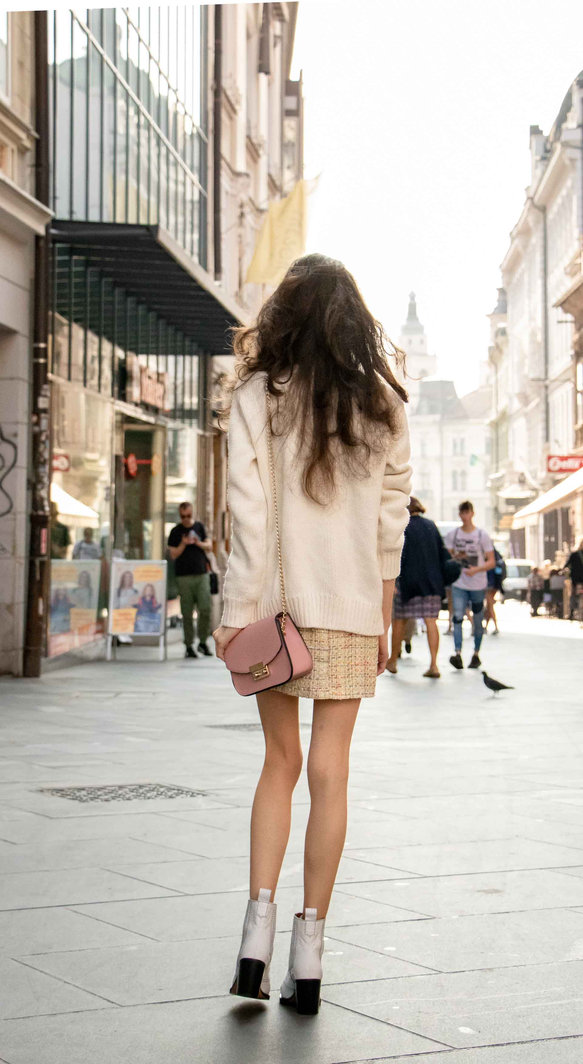 Beautiful Slovenian Fashion Blogger Veronika Lipar of Brunette from Wall wearing white Ganni Western boots, yellow tweed skirt, white turtleneck sweater, chain strap shoulder bag for brunch on the street in the morning in Ljubljana in fall