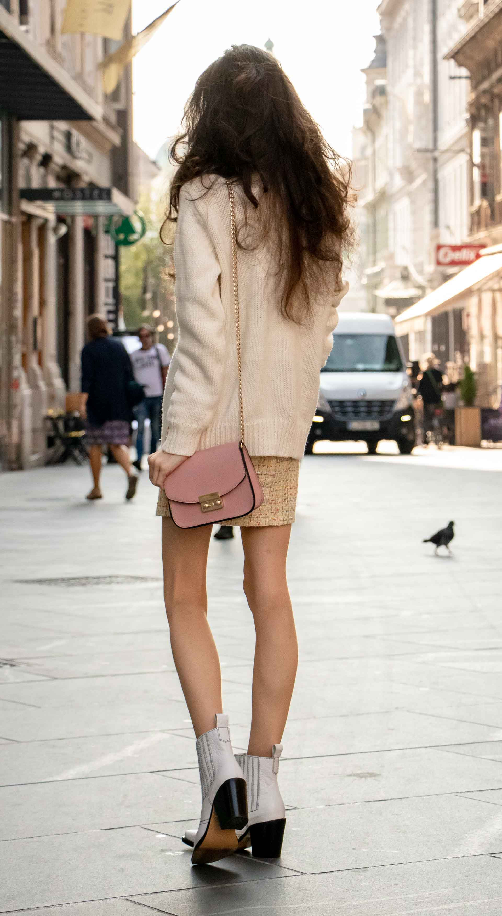 Beautiful Slovenian Fashion Blogger Veronika Lipar of Brunette from Wall wearing white Ganni Western boots, yellow tweed skirt, white turtleneck sweater, chain strap shoulder bag standing on the street in the morning in Ljubljana in fall