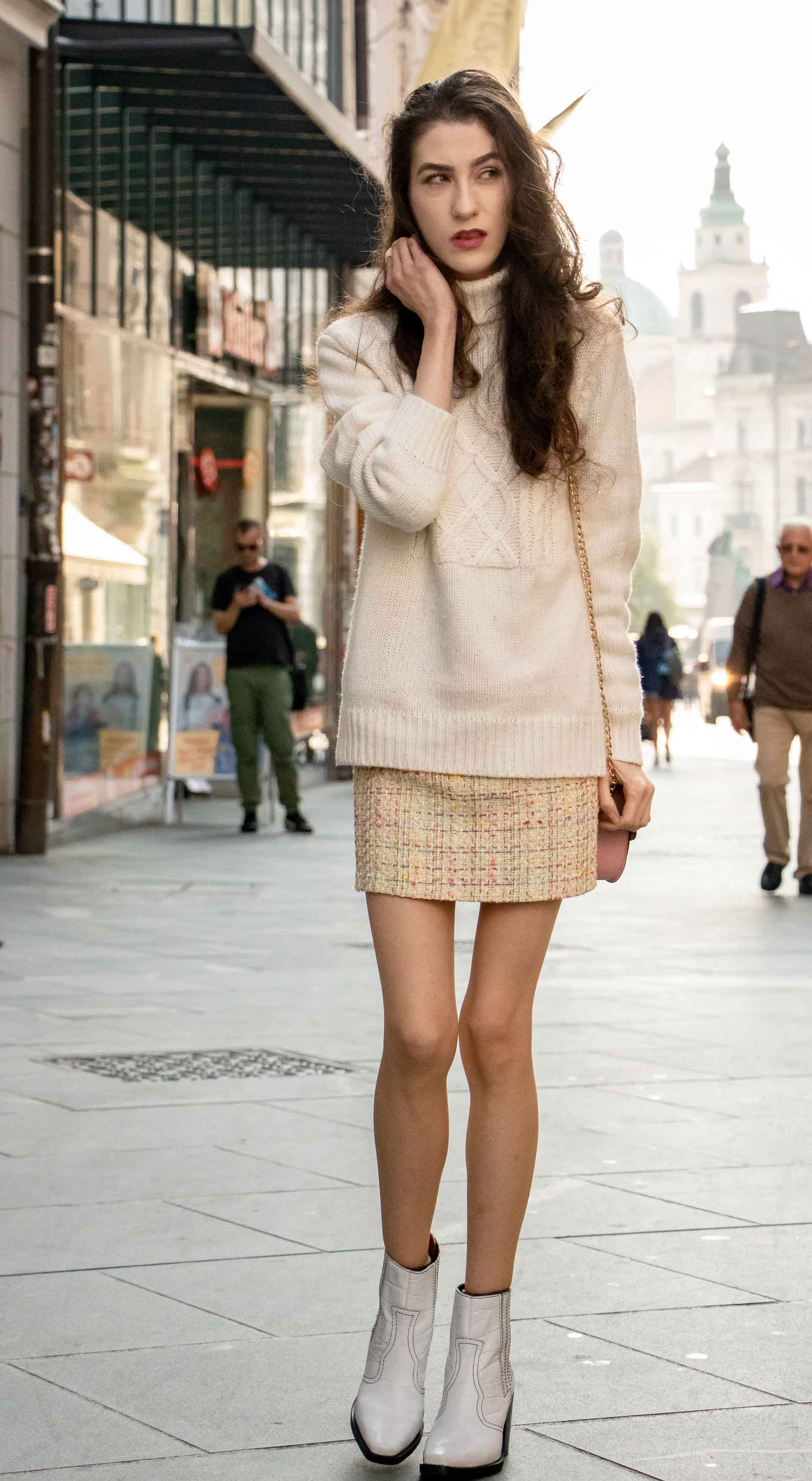 Beautiful Slovenian Fashion Blogger Veronika Lipar of Brunette from Wall dressed in white Ganni Western boots, yellow tweed skirt, white turtleneck sweater, chain strap shoulder bag on the street in the morning in Ljubljana in autumn
