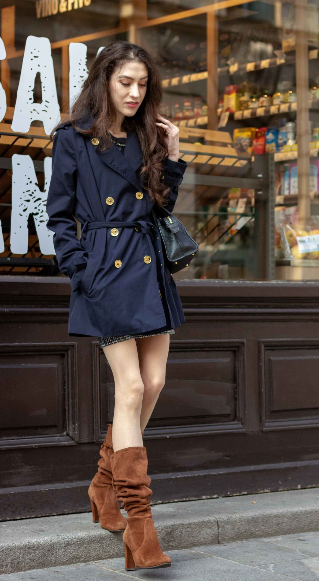 Beautiful Slovenian Fashion Blogger Veronika Lipar of Brunette from Wall wearing Stuart Weitzman brown slouchy boots, blue Michael Kors trench coat, black top handle bag while standing on the street