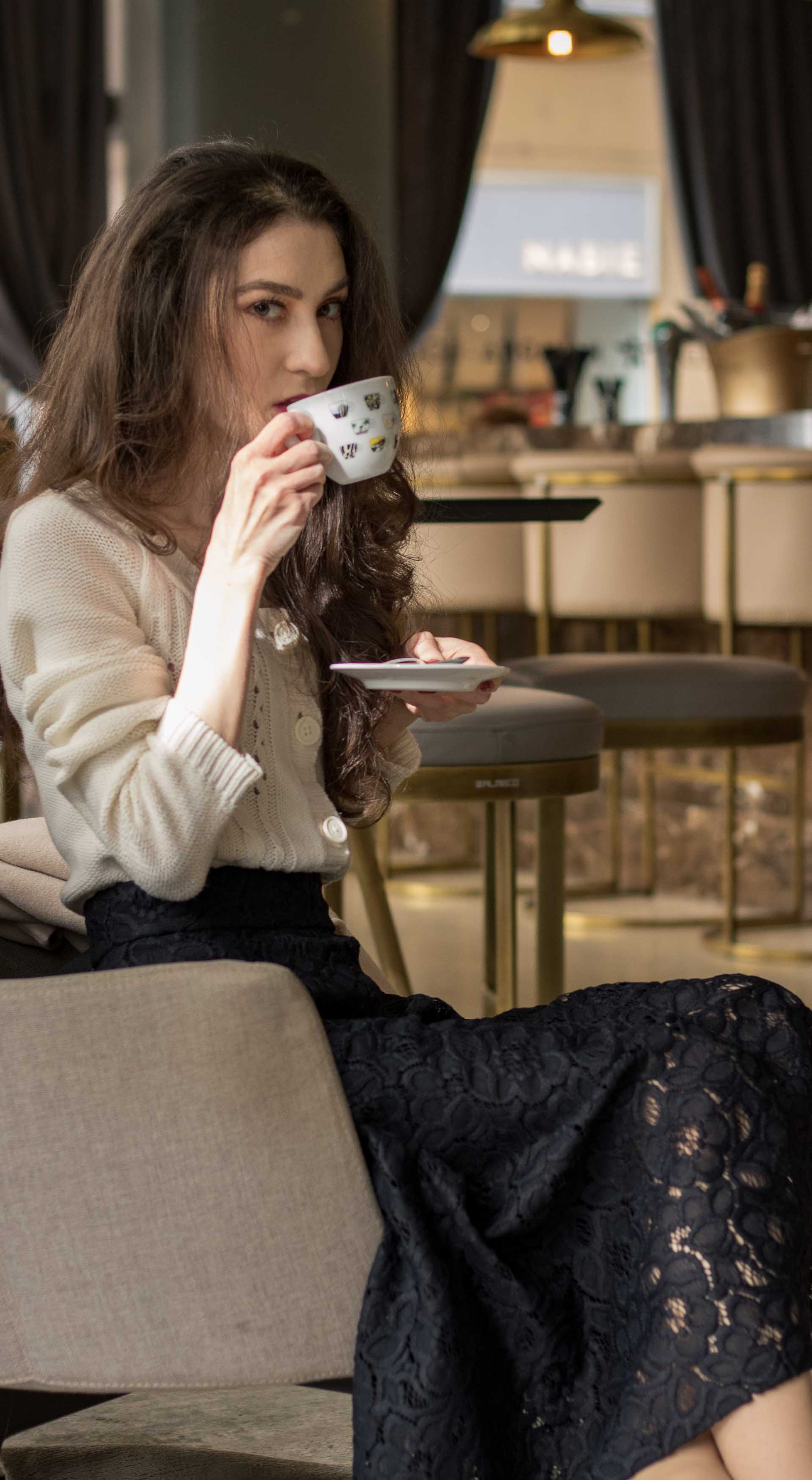 Beautiful Slovenian Fashion Blogger Veronika Lipar of Brunette from Wall wearing white MAngo cardigan etude into black lace midi skirt, blue Gianvito Rossi pumps for fall Sunday brunch drinking coffee