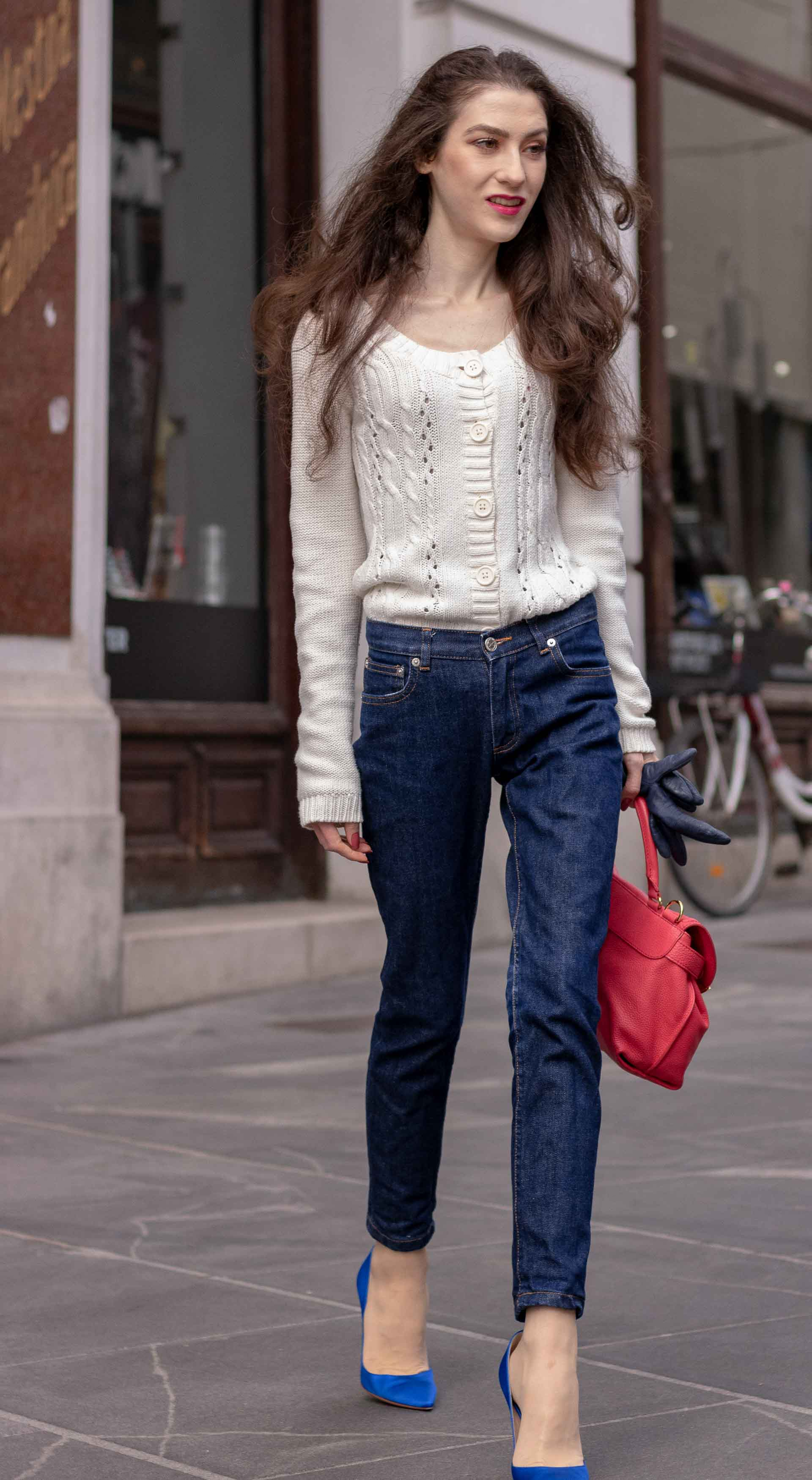 Beautiful Slovenian Fashion Blogger Veronika Lipar of Brunette from Wall dressed in white Mango cardigan tucked into dark blue denim jeans from a.p.c., blue Gianvito Rossi pumps, pink top handle bag walking on the street