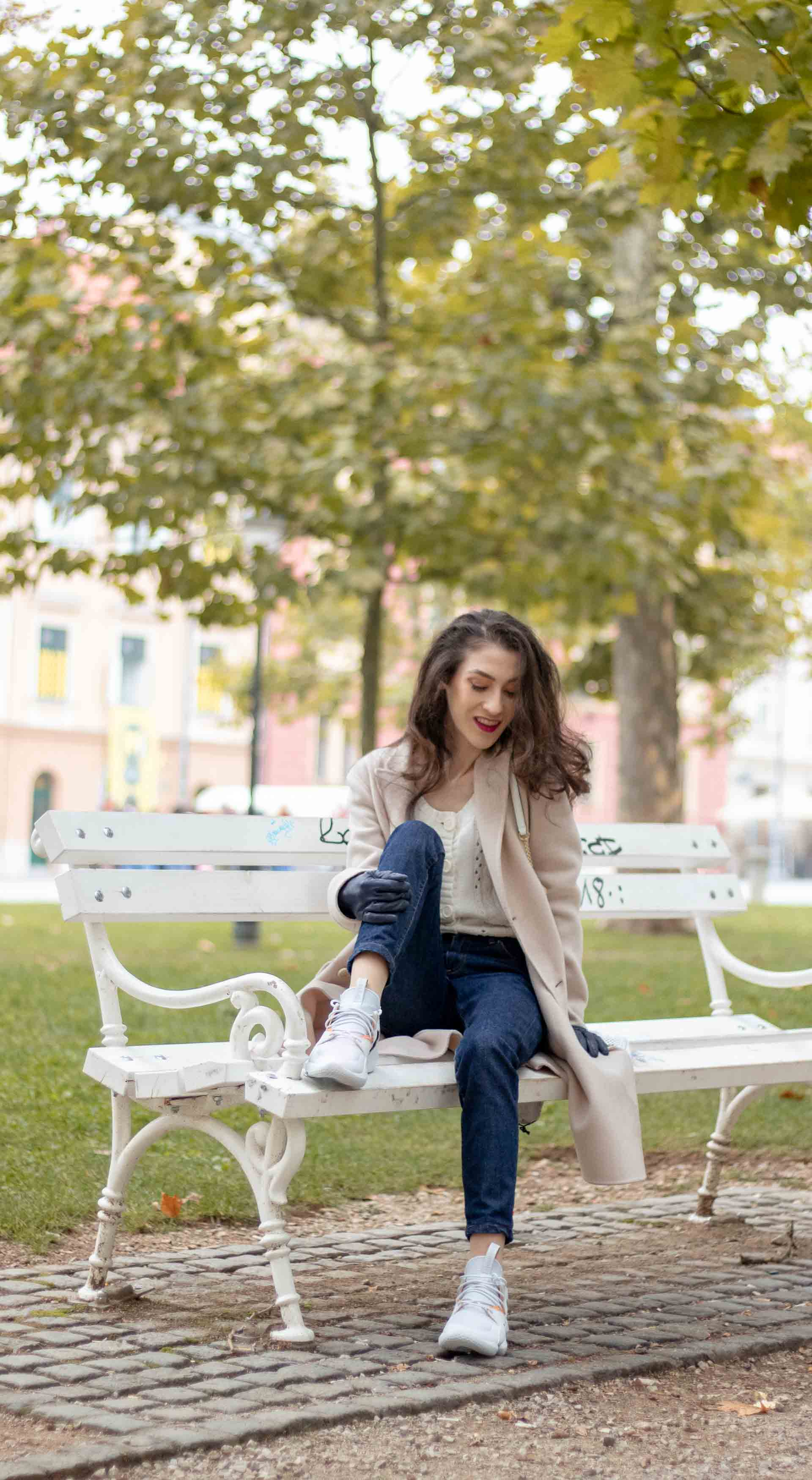 Beautiful Slovenian Fashion Blogger Veronika Lipar of Brunette from Wall dressed in white Mango cardigan tucked into A.P.C. dark blue denim jeans, Weekend Max Mara coat, Reebok instapump having fun in park