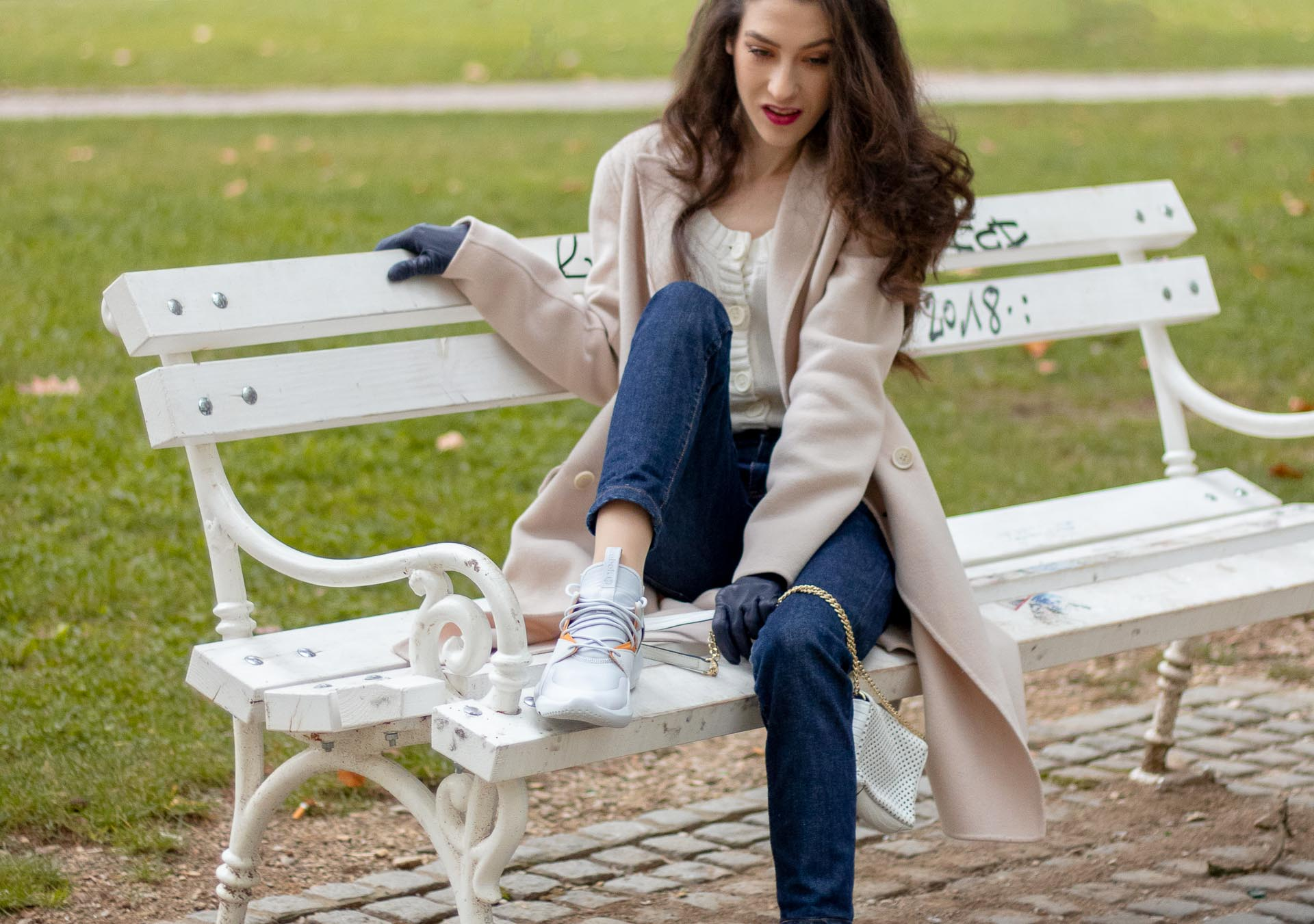 Beautiful Slovenian Fashion Blogger Veronika Lipar of Brunette from Wall wearing white Mango cardigan tucked into dark blue denim jeans from a.p.c., Weekend Max Mara coat, Reebok instapump sneakers casually