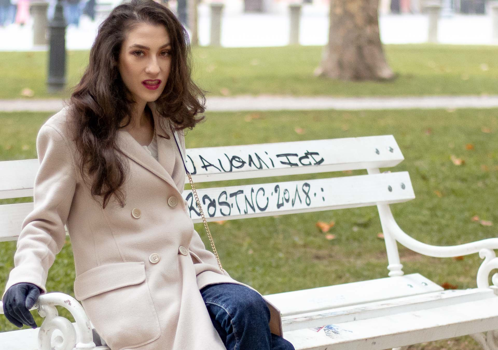 Beautiful Slovenian Fashion Blogger Veronika Lipar of Brunette from Wall dressed in white Mango cardigan tucked into A.P.C. dark blue denim jeans, Weekend Max Mara coat, Reebok instapump in park