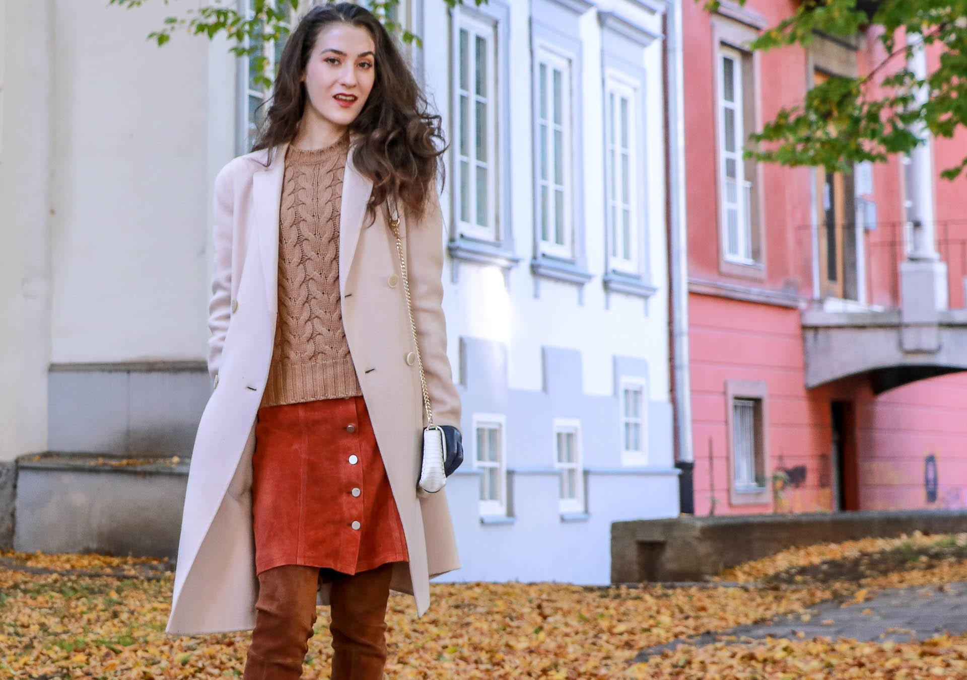 Beautiful Slovenian Fashion Blogger Veronika Lipar of Brunette from Wall wearing Max Mara camel cable knit sweater, front button brown suede skirt, Stuart Weitzman brown over the knee boots, Max Mara coat standing on the leaves