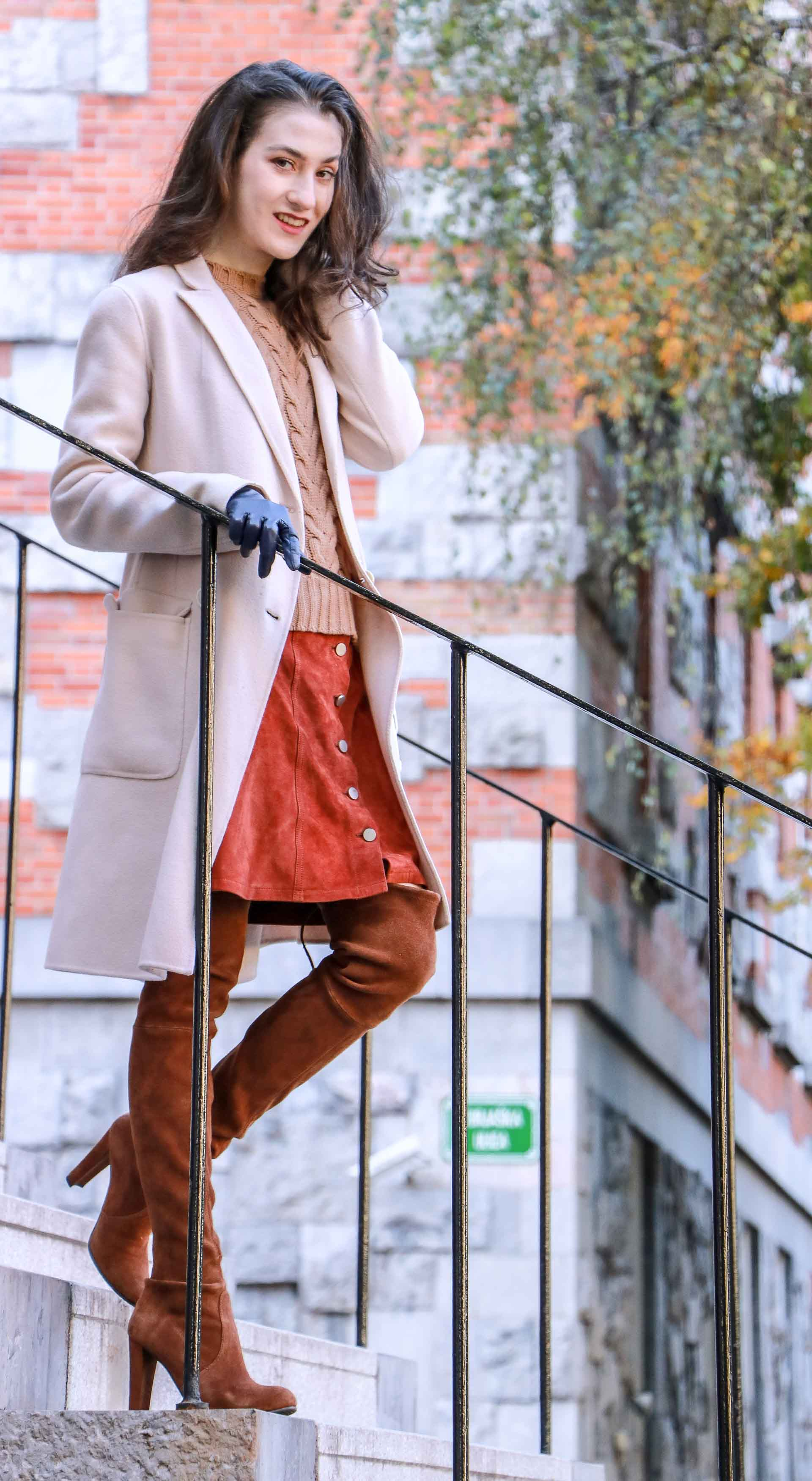 Beautiful Slovenian Fashion Blogger Veronika Lipar of Brunette from Wall wearing Max Mara camel cable knit sweater, front button brown suede skirt, Stuart Weitzman brown over the knee boots, Max Mara coat standing on the stairs