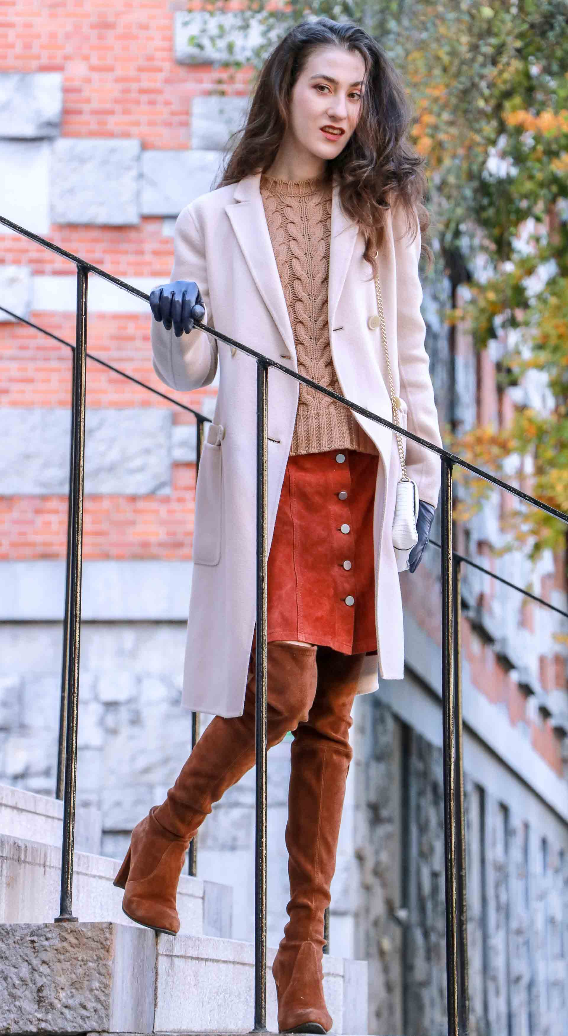 Beautiful Slovenian Fashion Blogger Veronika Lipar of Brunette from Wall dressed in Max Mara camel cable knit sweater, front button brown suede skirt, Stuart Weitzman brown over the knee boots, Max Mara coat standing on the stairs