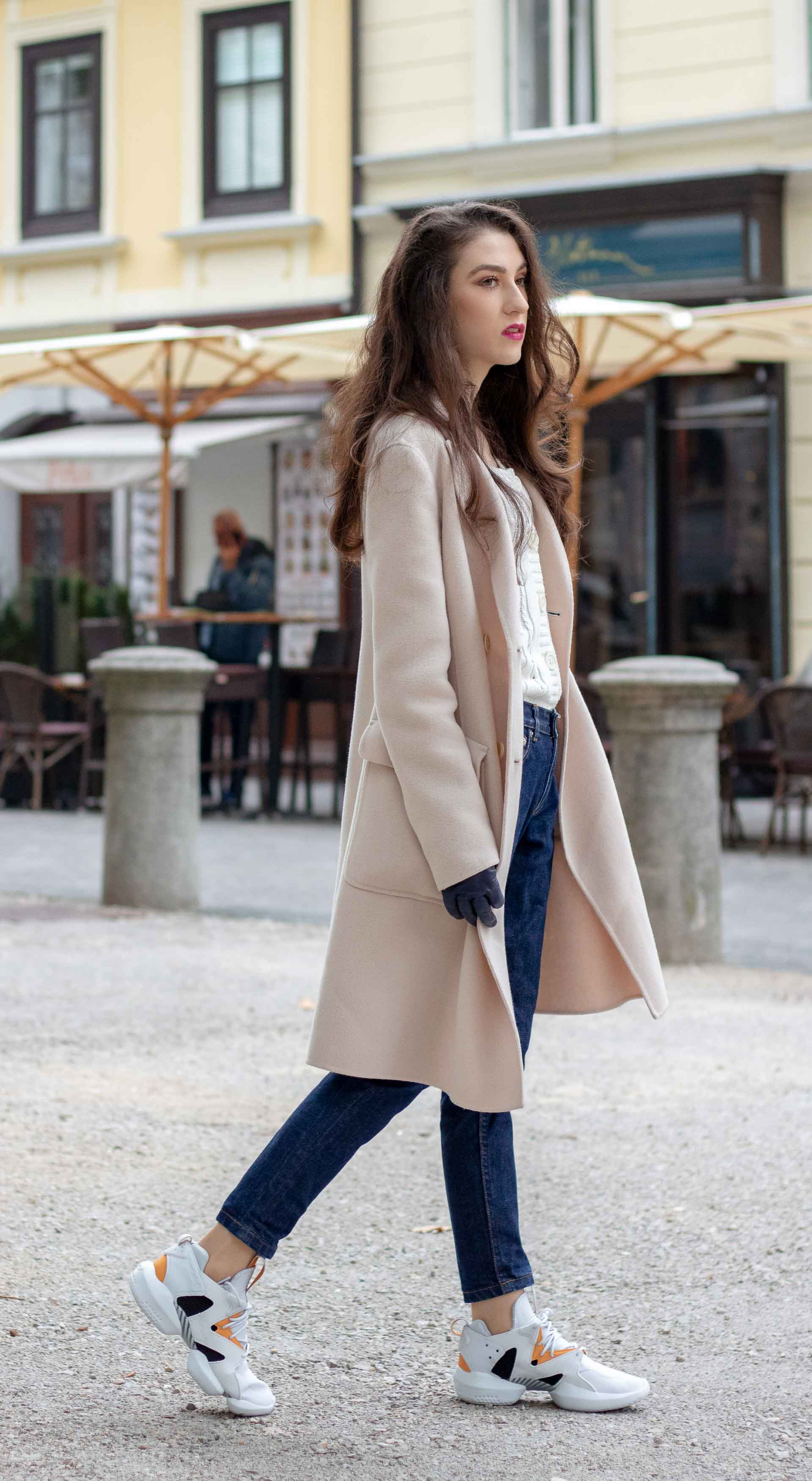 Beautiful Slovenian Fashion Blogger Veronika Lipar of Brunette from Wall wearing white Mango cardigan tucked into dark blue denim jeans from a.p.c., Weekend Max Mara coat, Reebok instapump sneakers in casually