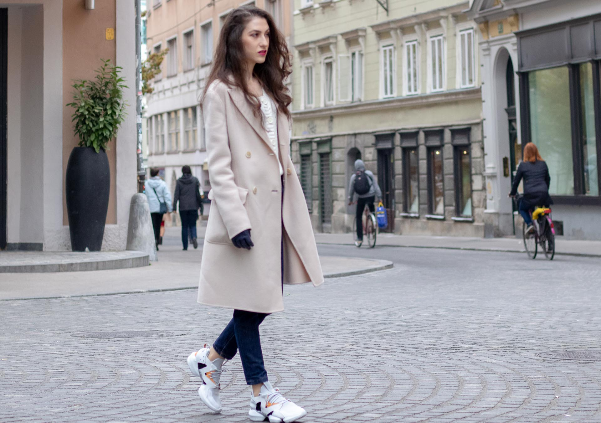 Beautiful Slovenian Fashion Blogger Veronika Lipar of Brunette from Wall dressed in white Mango cardigan tucked into A.P.C. dark blue denim jeans, Weekend Max Mara coat, Reebok instapump crossing road in Ljubljana
