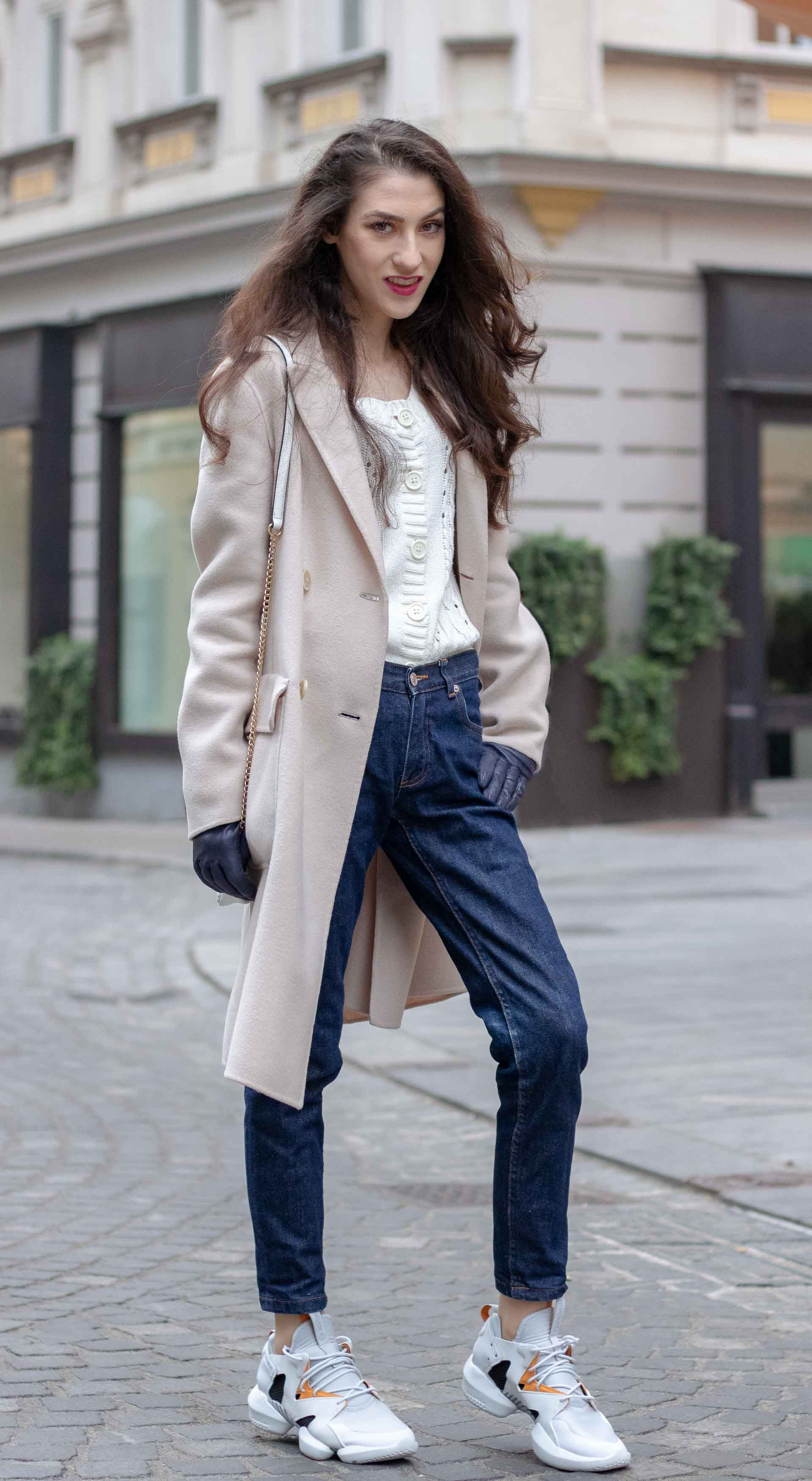 Beautiful Slovenian Fashion Blogger Veronika Lipar of Brunette from Wall dressed in white Mango cardigan tucked into A.P.C. dark blue denim jeans, Weekend Max Mara coat, Reebok instapump in Ljubljana